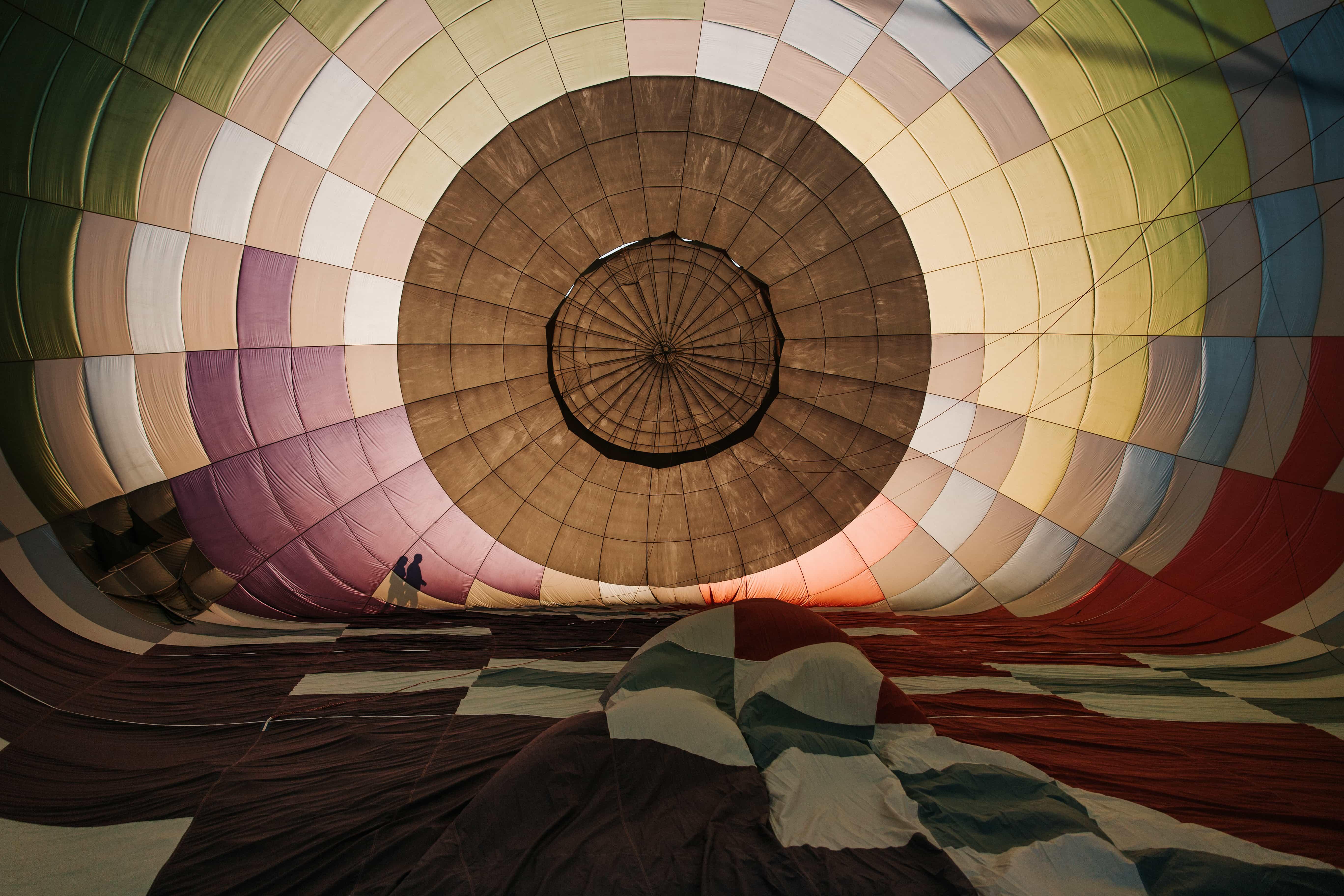 Silhouette of couple walking behind hot air balloon, hot air balloon elopement in Boulder, Colorado