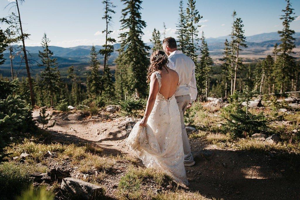 Sunspot Lodge Winter Park Resort Wedding bride and groom walking on mountain bike path trail through woods