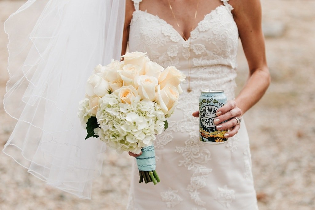 Bride holding her wedding bouquet and a beer can