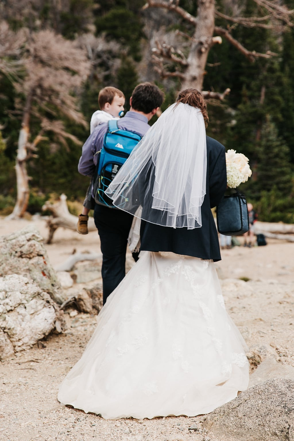 Bride and groom hiking back with their son after their St. Mary's Glacier elopement hiking wedding in Colorado