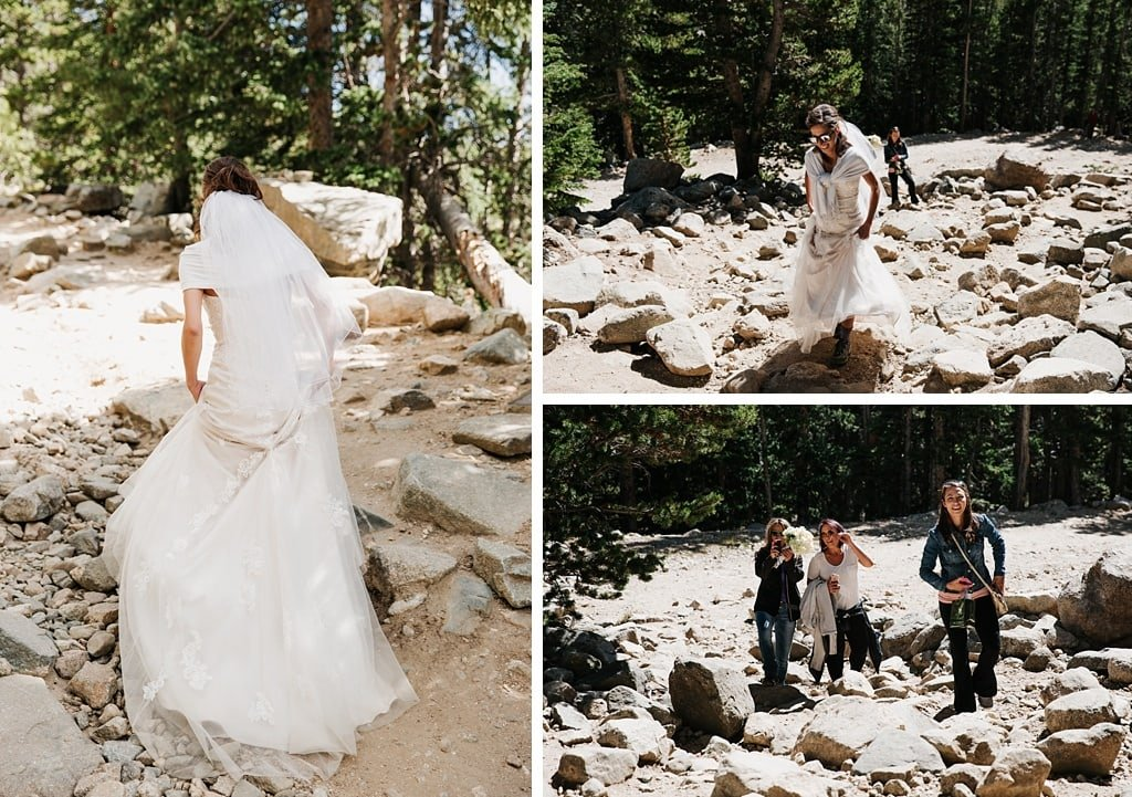 Bride hiking the St. Mary's Glacier trail with friends for her Colorado mountain elopement