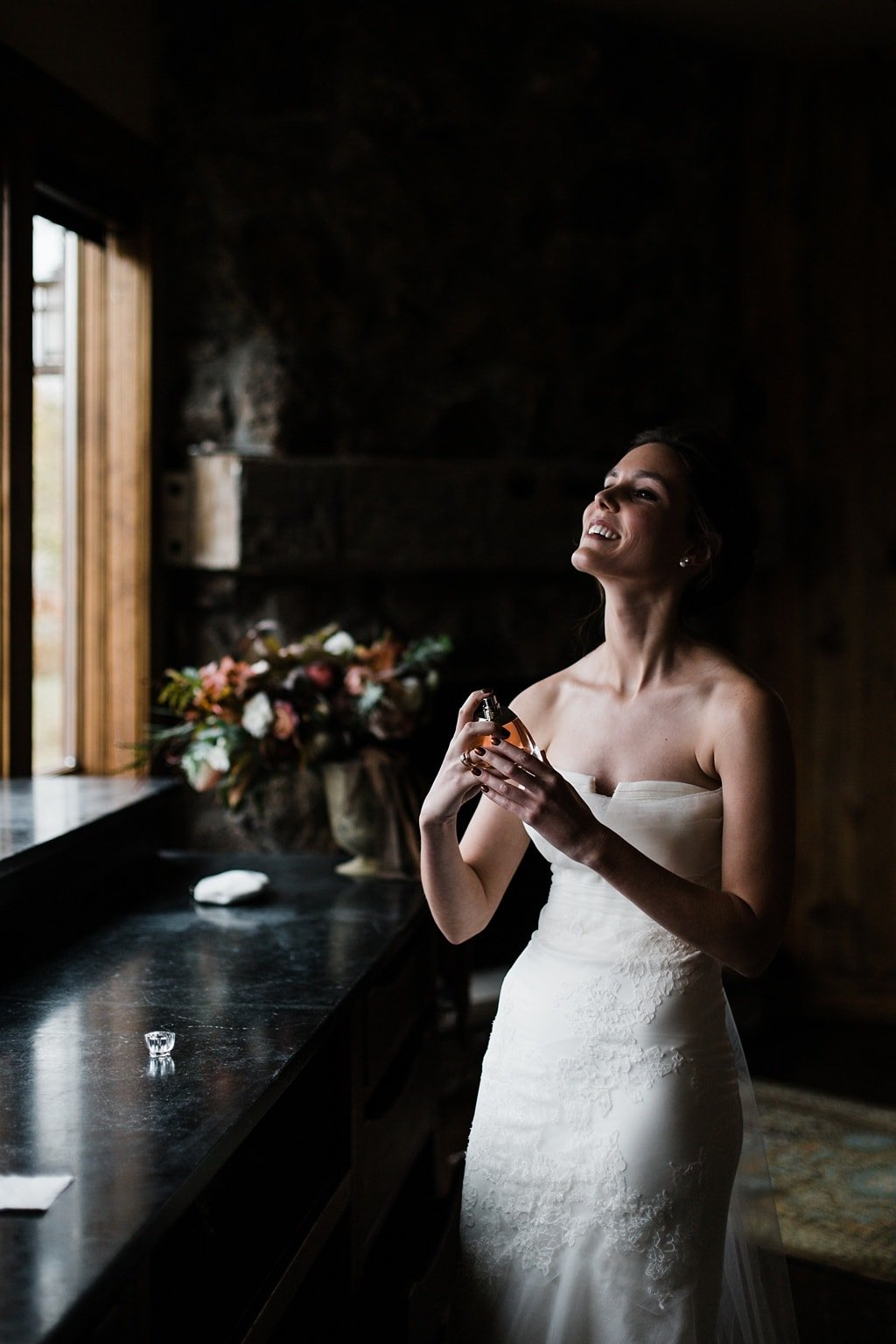 Bride putting on perfume getting ready at Devil's Thumb Ranch in Tabernash Colorado documentary wedding photography