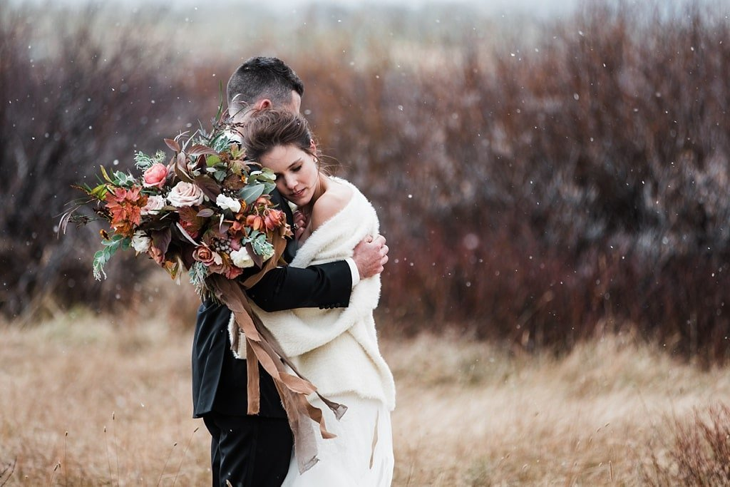 Bride and groom wedding photography portraits hugging in winter with Vera Wang wedding dress and bouquet by Yonder House florals Colorado