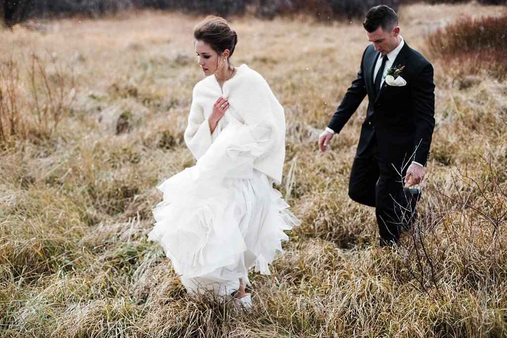 Bride and groom portraits walking through field near Devil's Thumb Ranch in Tabernash Colorado
