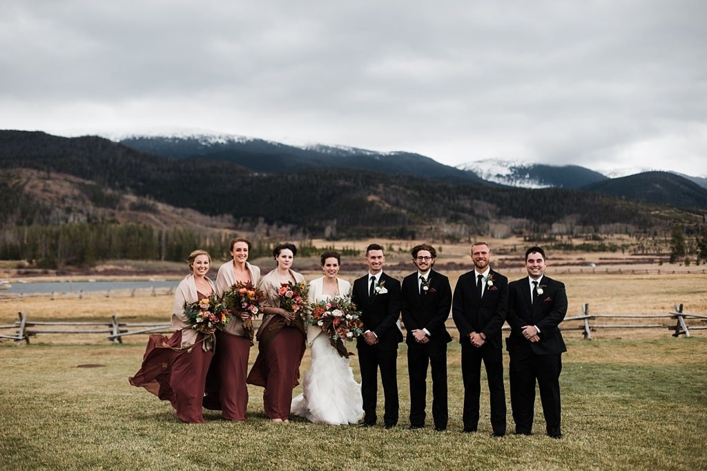 Bride and groom with bridal party men in black suits bridesmaids in muted wine colored dresses bouquets by Yonder House bridesmaid dresses by Jenny Yoo