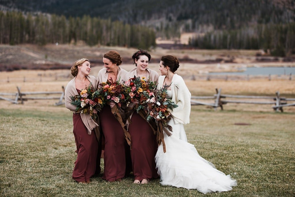 Bride with bridesmaids at Devil's Thumb Ranch, muted wine colored dresses, bouquets by Yonder House Colorado wedding photography bridesmaid dresses by Jenny Yoo