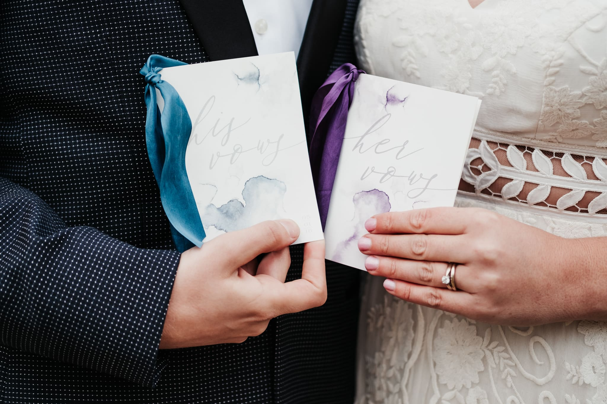 Bride and groom holding his and her vow books by XO Wyo + Co