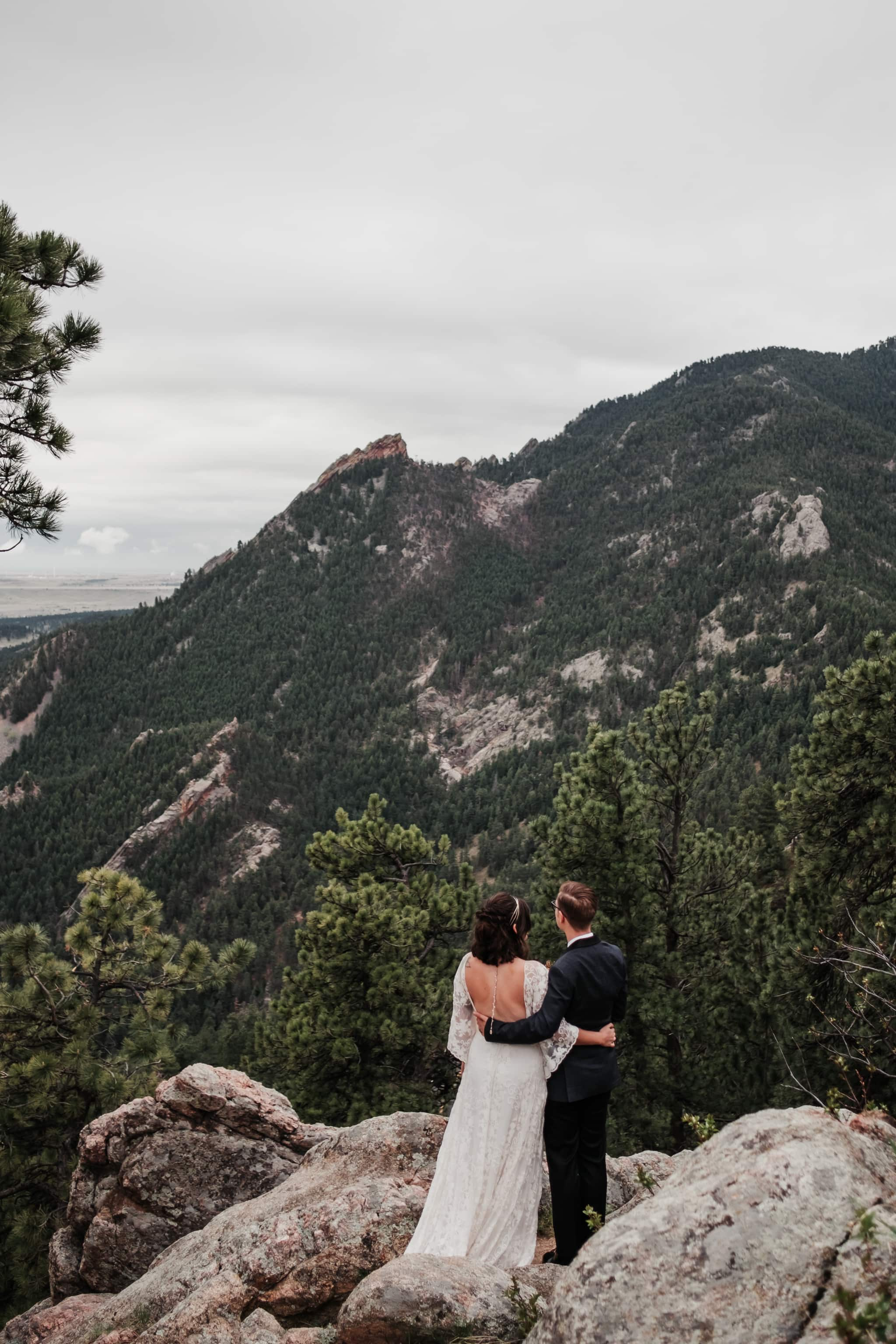 Hiking elopement photography, bride and groom hiking a mountain, Colorado wedding photographer, bride and groom looking at Boulder Flatirons