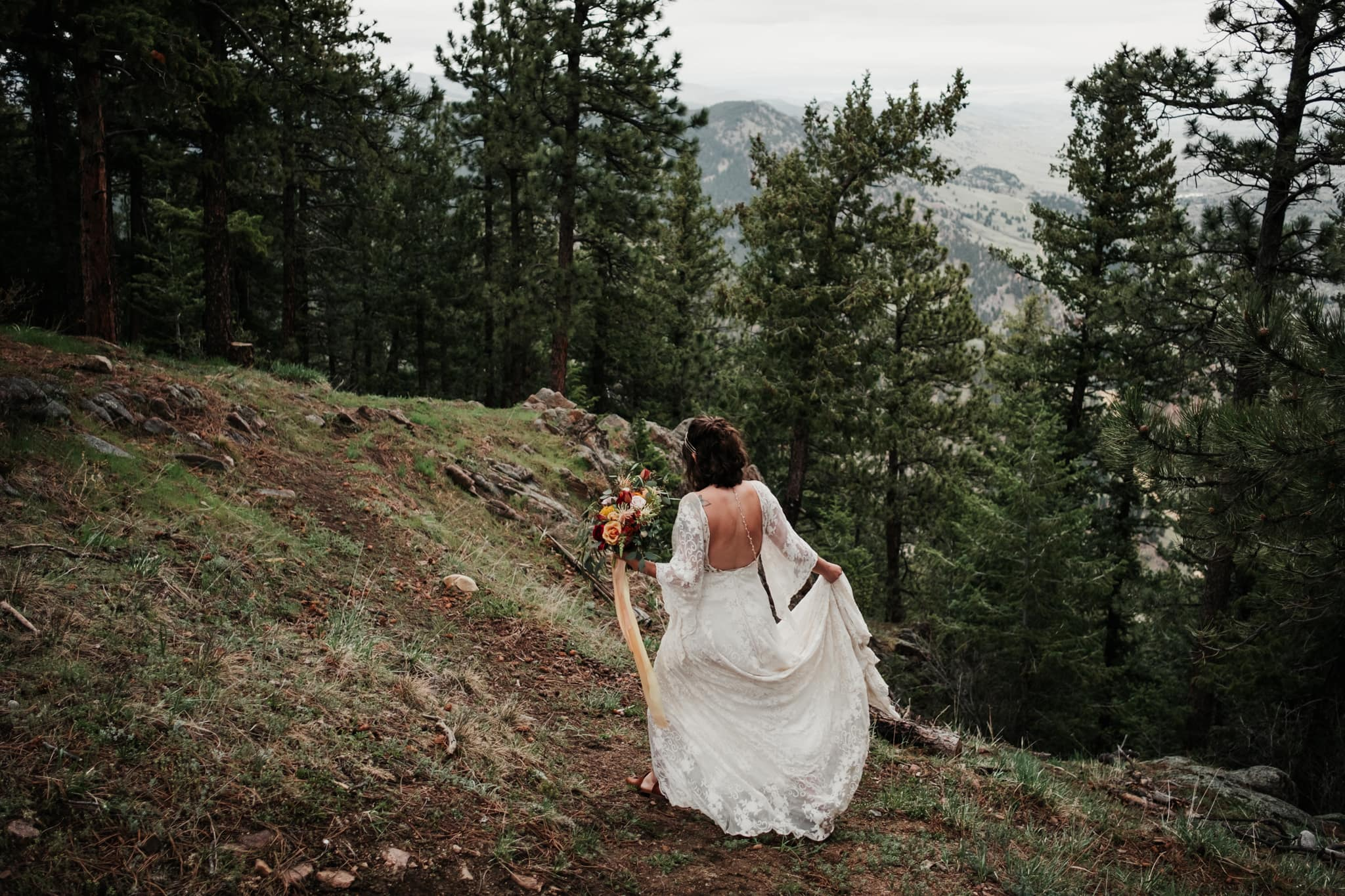 Bride hiking through forest in Rue de Seine bridal gown, Colorado elopement photographer