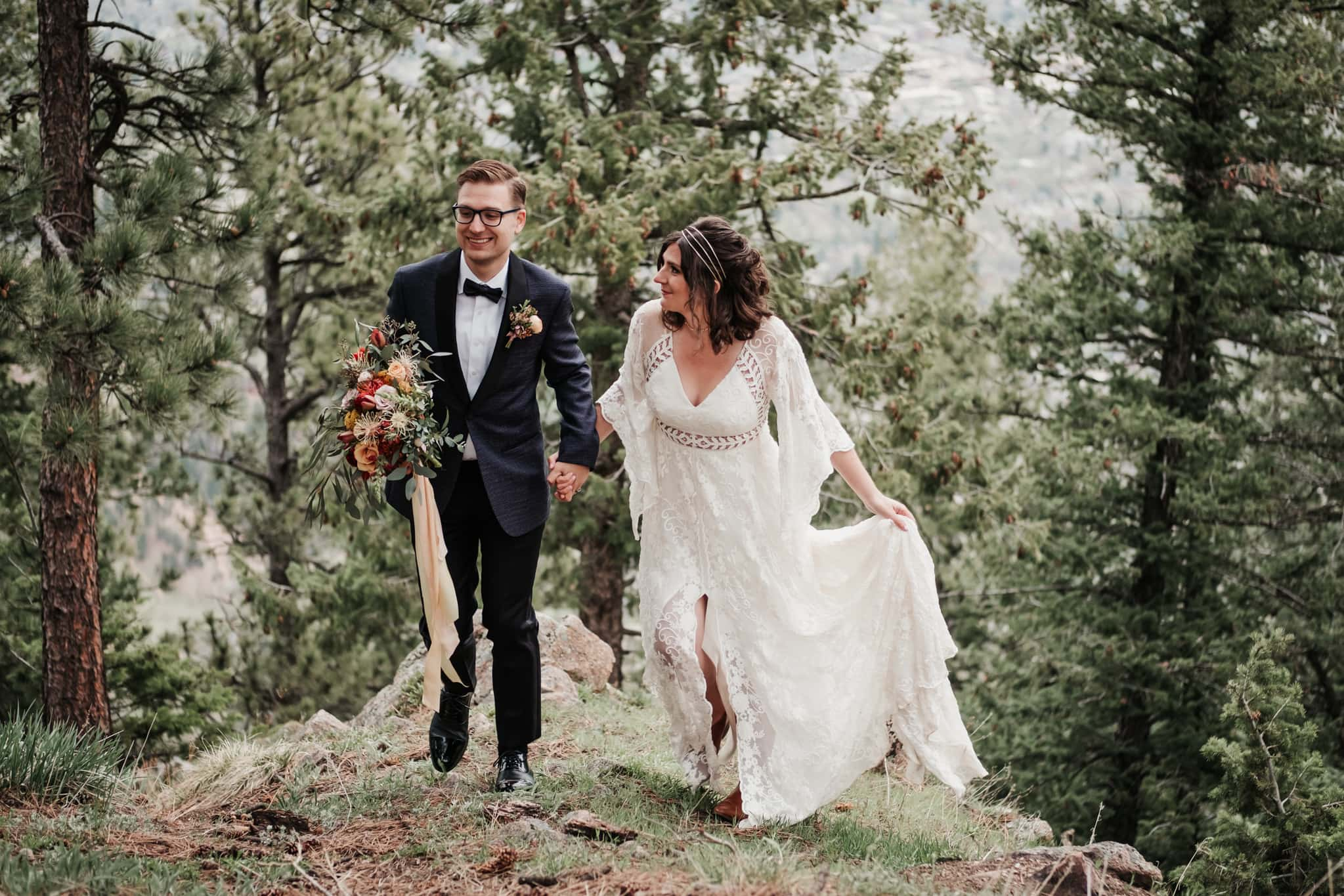 Bride and groom hiking through the woods, Colorado mountain elopement photographer