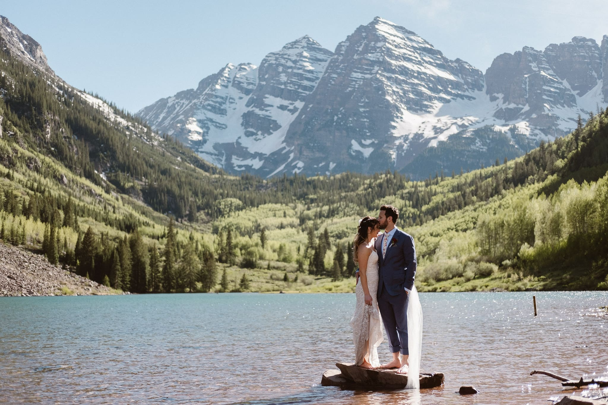 Maroon Bells Amphitheater elopement, Aspen wedding photographer, Colorado adventure elopement, bride and groom standing on rock in alpine lake