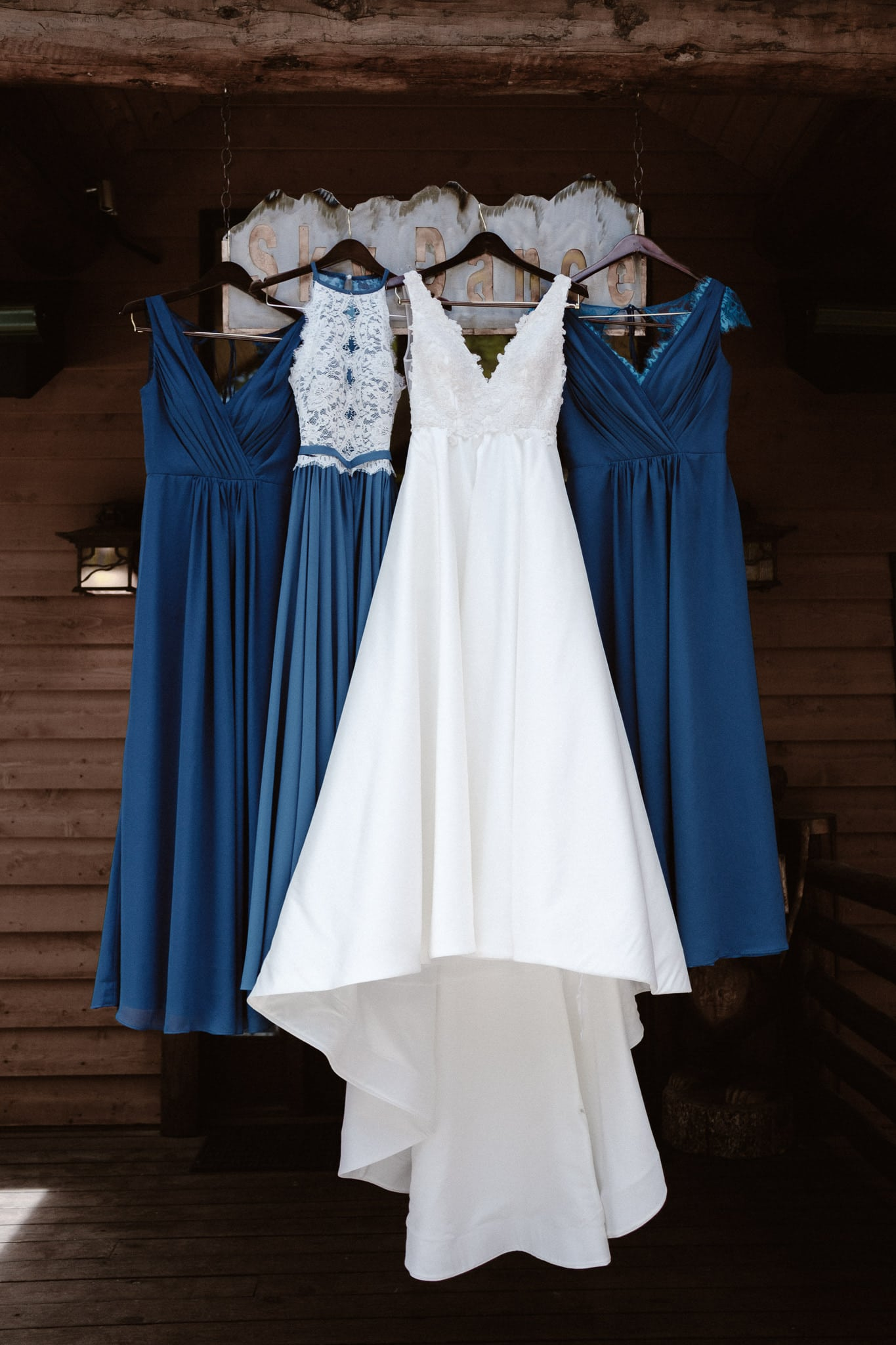 Wedding dress and dark blue bridesmaid dresses hanging at log cabin, Breckenridge wedding photographer