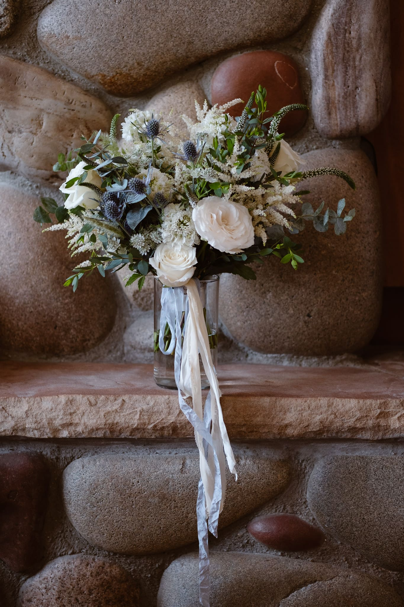 Bride's bouquet with green, cream, and pale blue flowers and hand dyed silk ribbons by Flora by Nora for Breckenridge Nordic Center wedding
