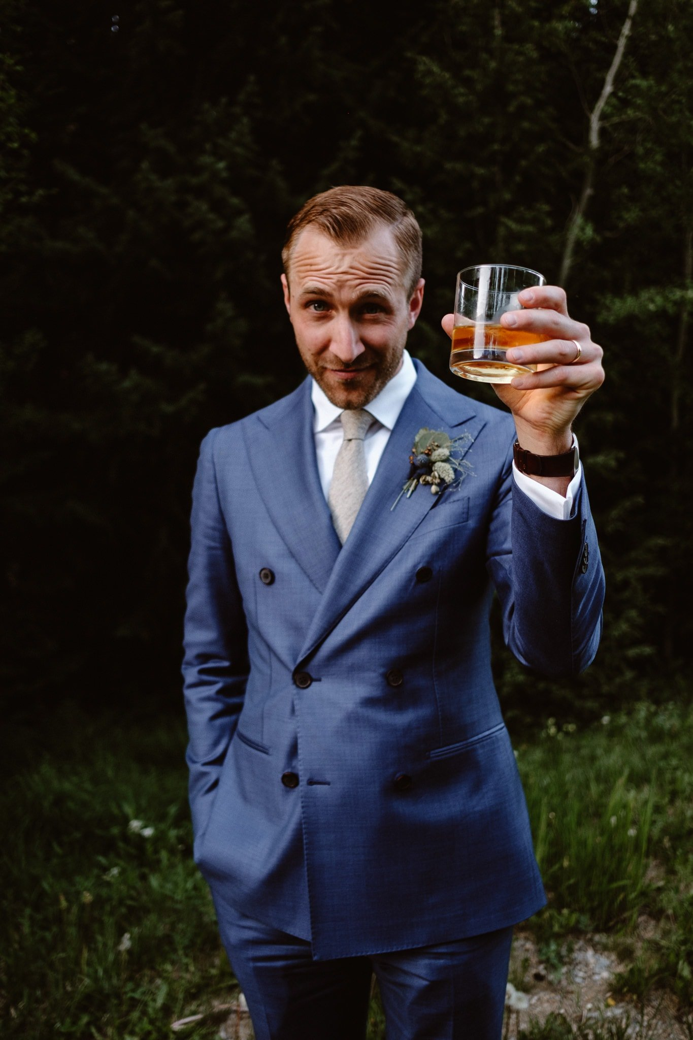 Groom in blue suit holding whiskey glass at Breckenridge Nordic Center wedding, Summit County wedding photographer