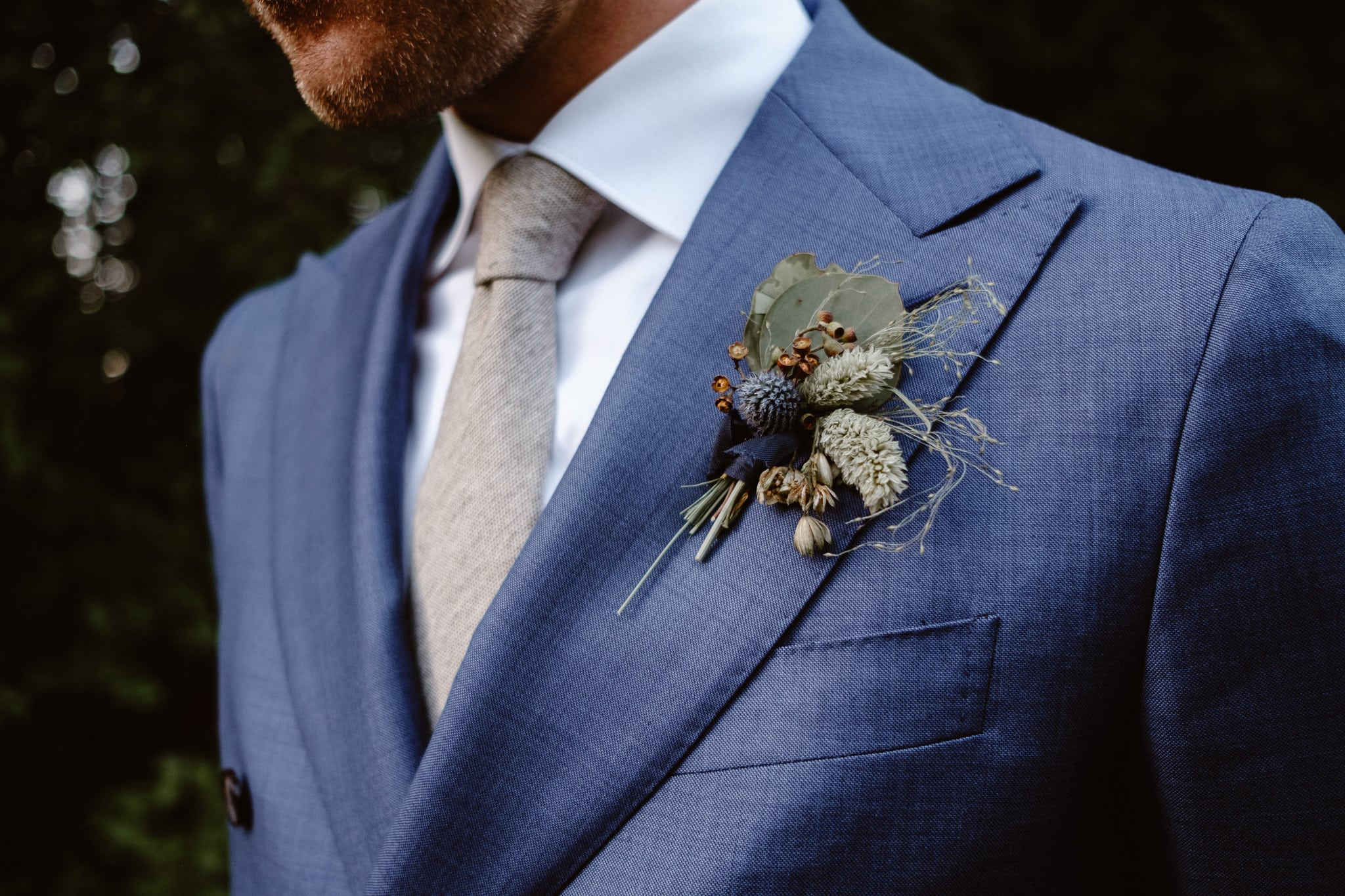 Groom wearing boutonniere by Flora by Nora at Breckenridge Nordic Center wedding, Summit County wedding photographer