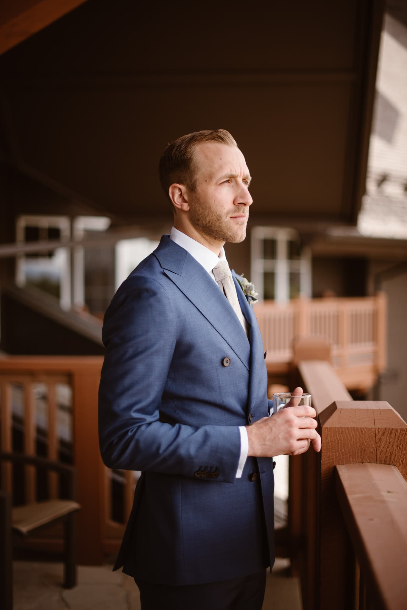 Groom in blue suit enjoying whiskey before Breckenridge Nordic Center wedding photography