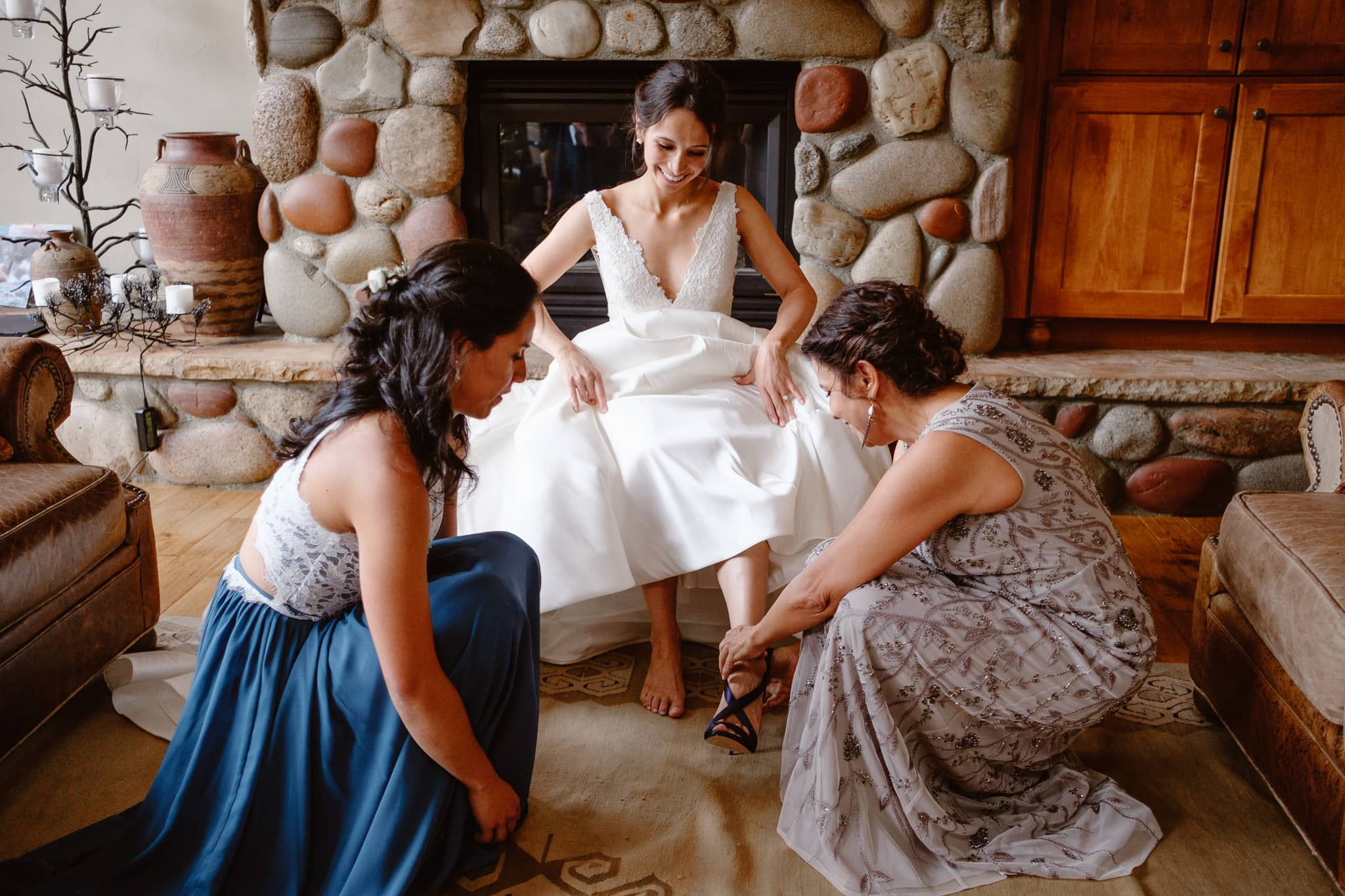 Bride's mom and sister helping her put shoes on for her Breckenridge Nordic Center wedding photography