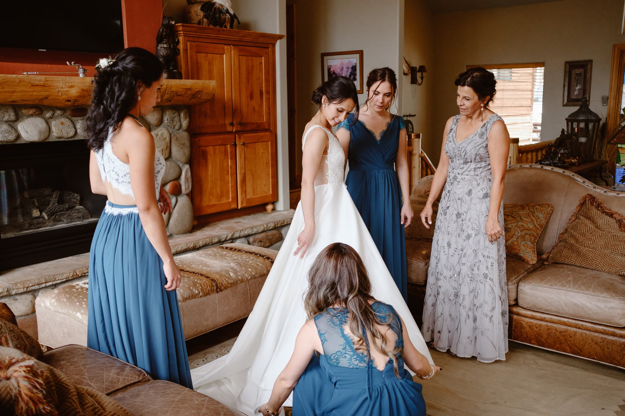 Bride with bridesmaids and her mom, putting wedding dress on for her Breckenridge Nordic Center wedding