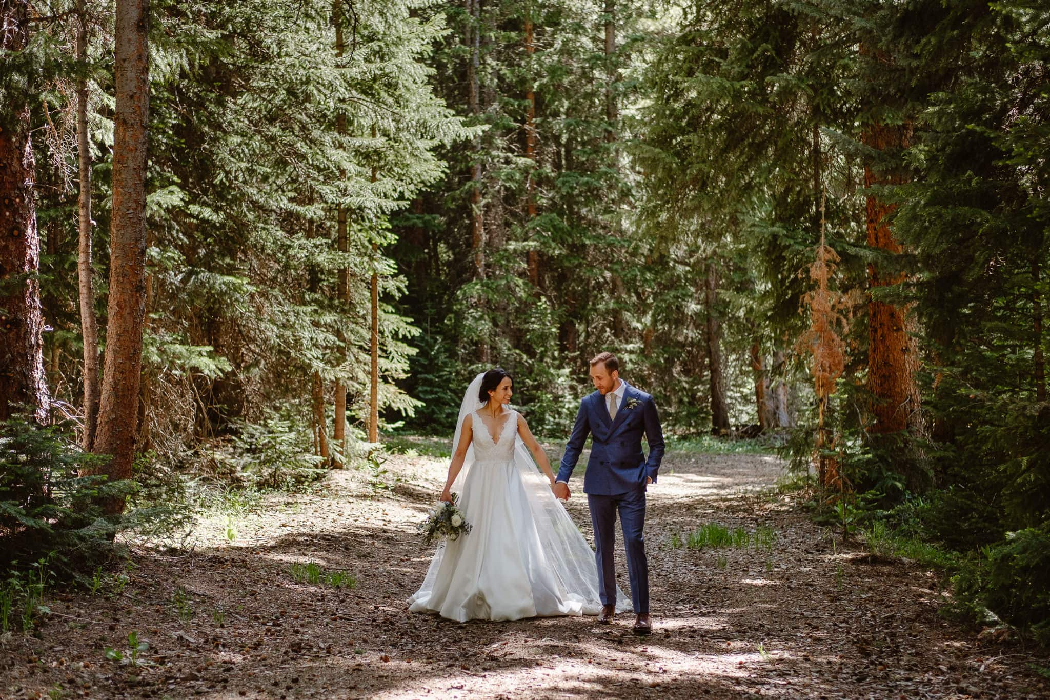 Bride and groom portraits walking in the woods at Breckenridge Nordic Center wedding, Summit County wedding photographer