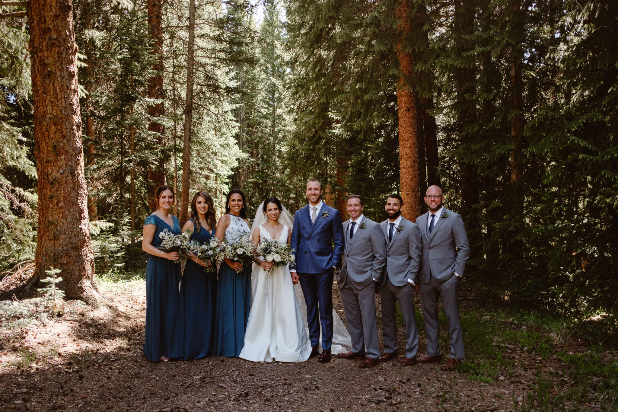 Bride and groom with their wedding party in the woods, Breckenridge Nordic Center wedding, Summit County wedding photographer