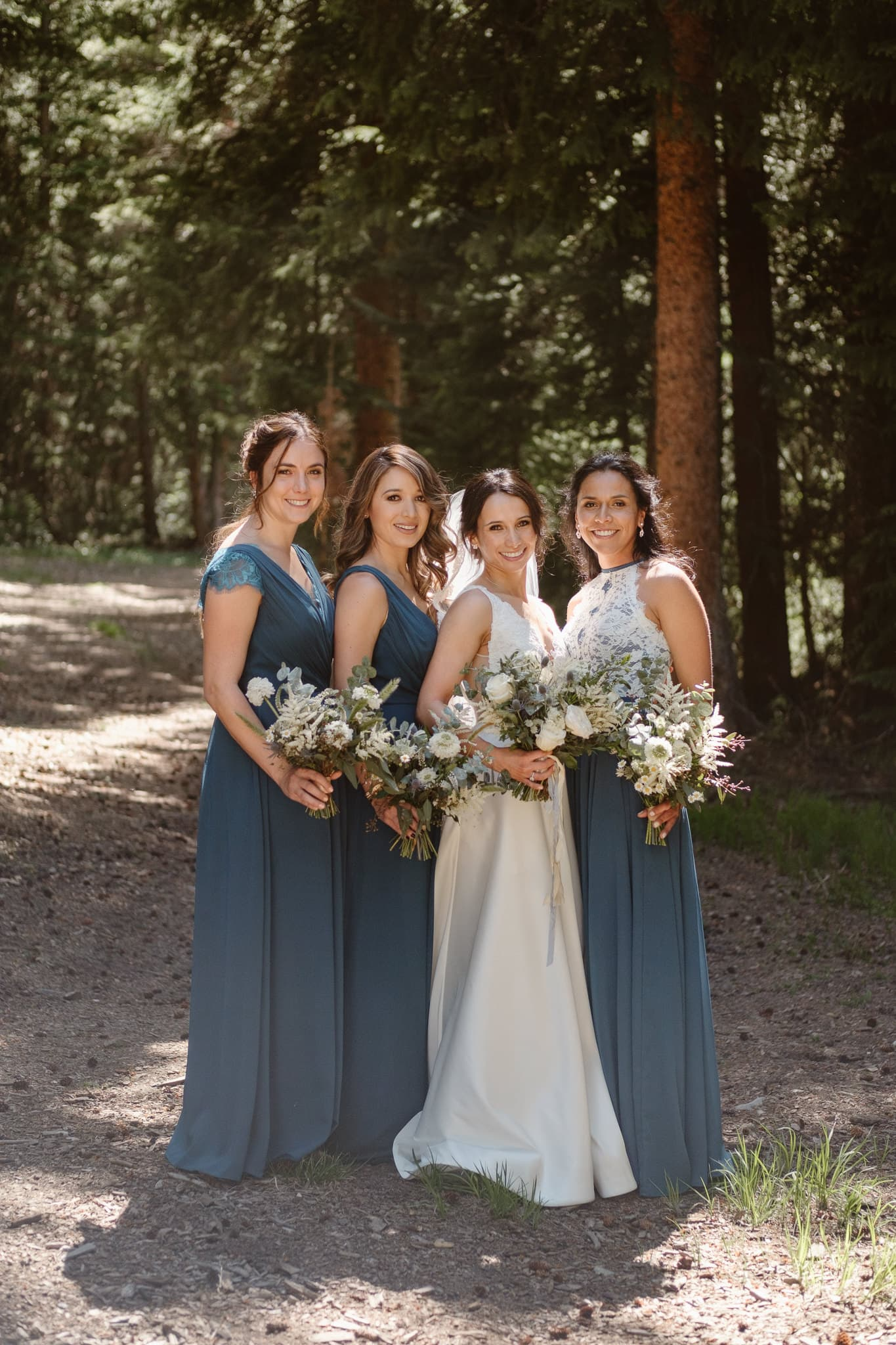Bride with bridesmaids in the woods, teal blue bridesmaid dresses, Breckenridge Nordic Center wedding, Summit County wedding photographer