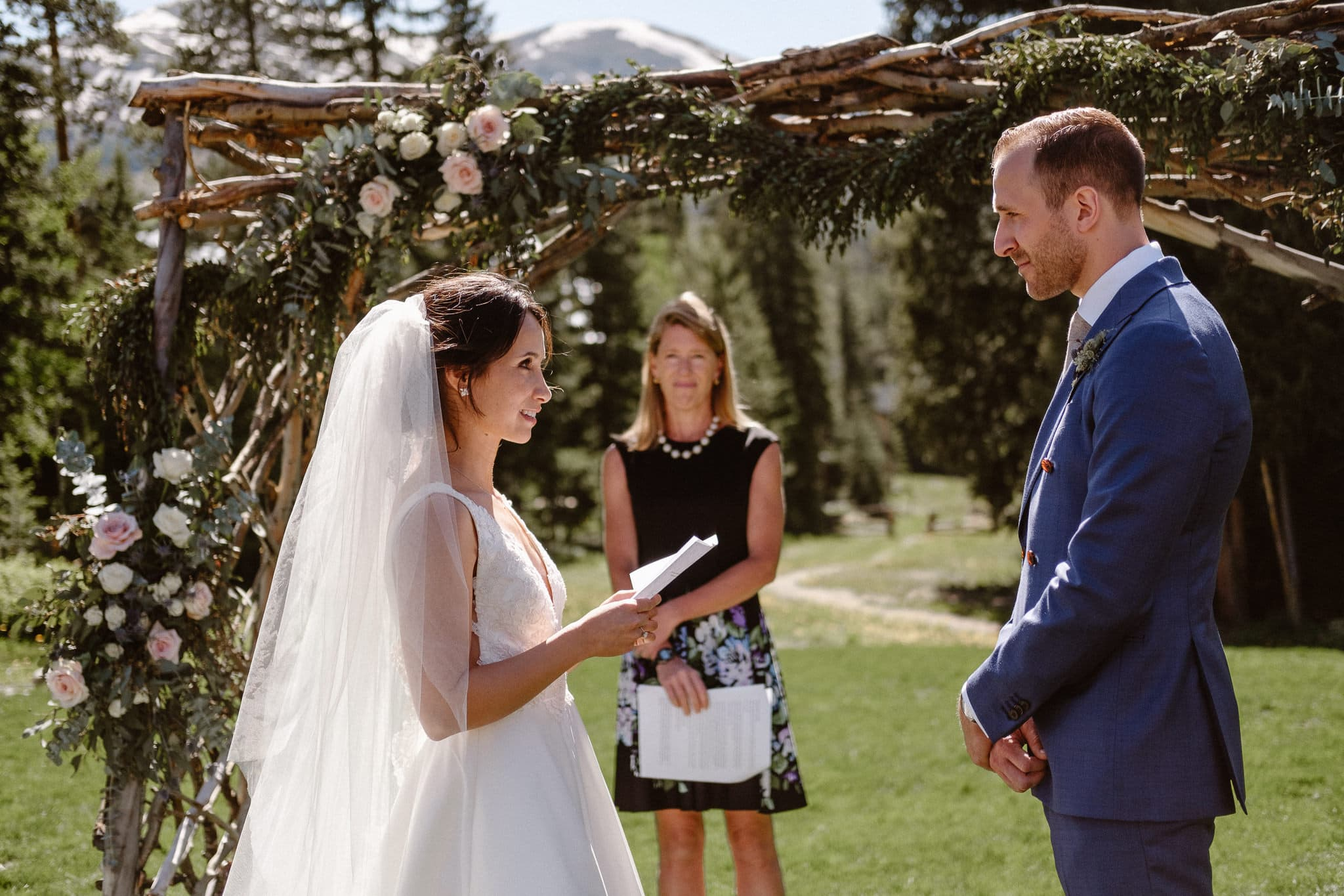 Bride and groom exchanging vows at Breckenridge Nordic Center wedding venue, outdoor log cabin wedding ceremony, Colorado wedding photographer