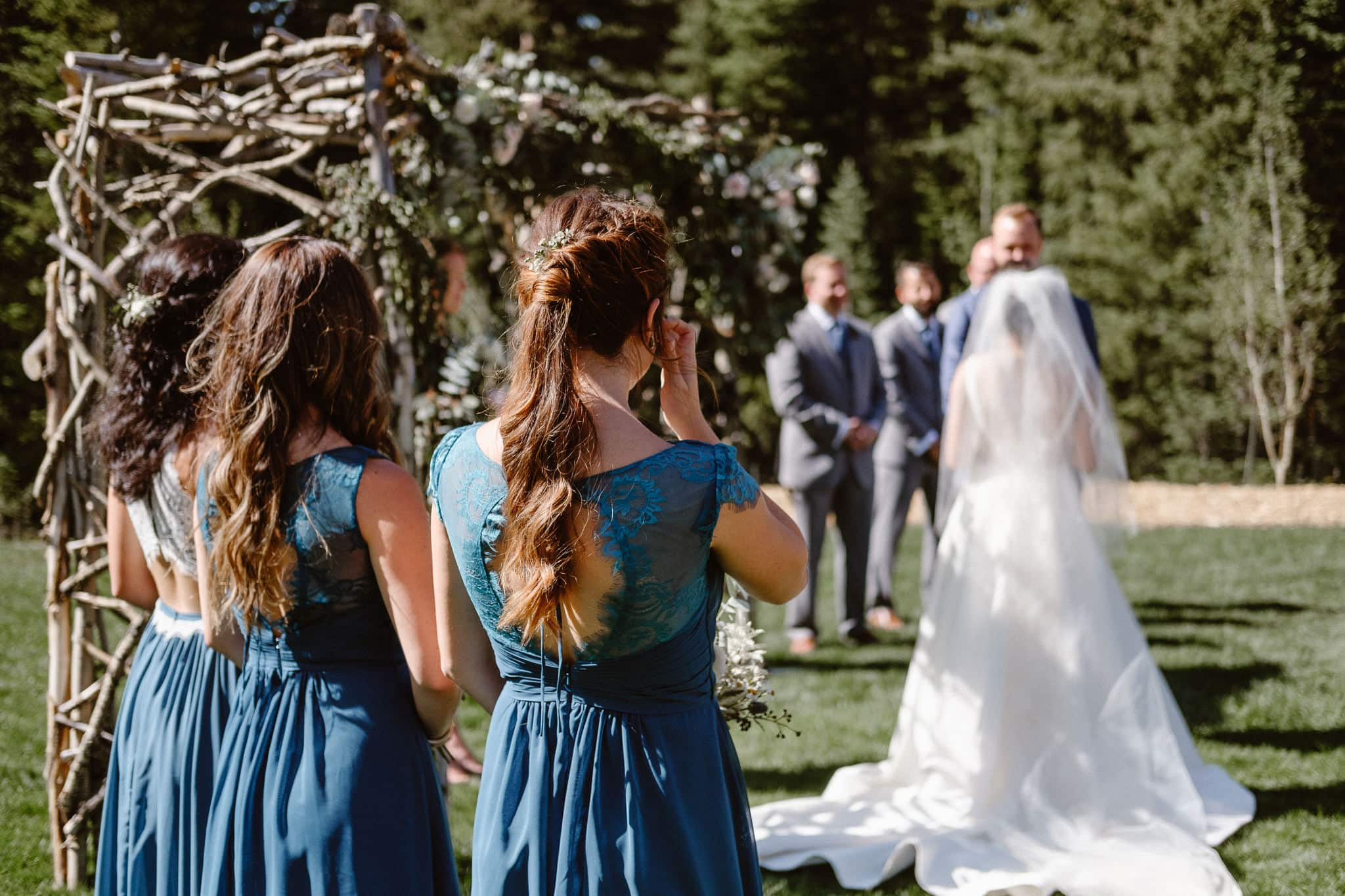 Bridesmaid wiping her tears at Breckenridge Nordic Center wedding venue, outdoor log cabin wedding ceremony, Colorado wedding photographer