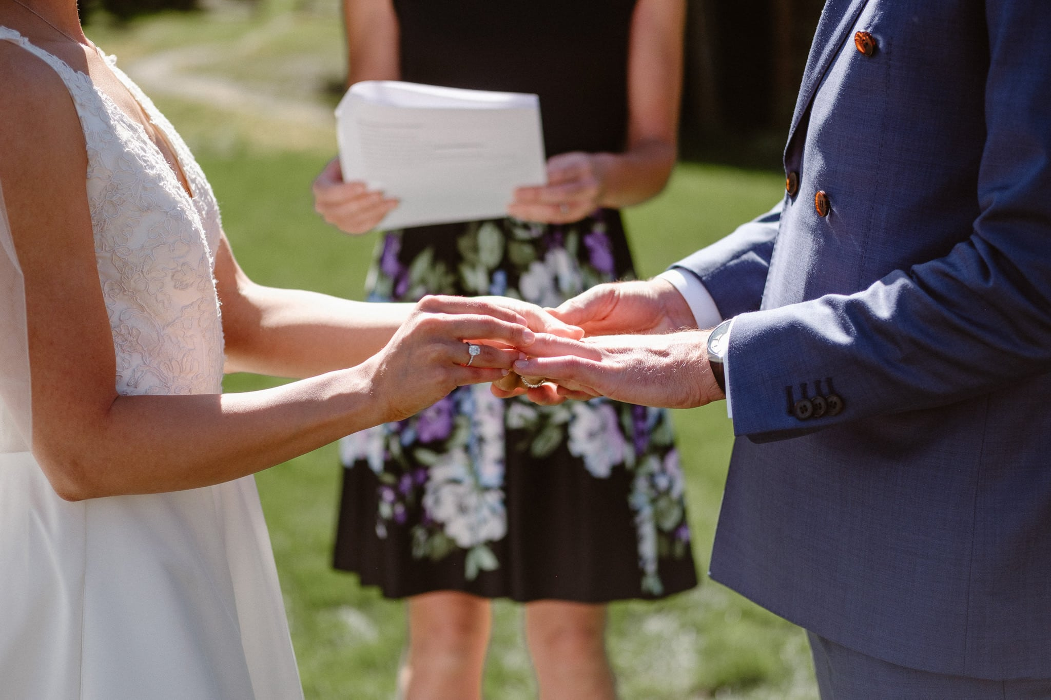 Bride and groom exchanging rings at Breckenridge Nordic Center wedding venue, outdoor log cabin wedding ceremony, Colorado wedding photographer