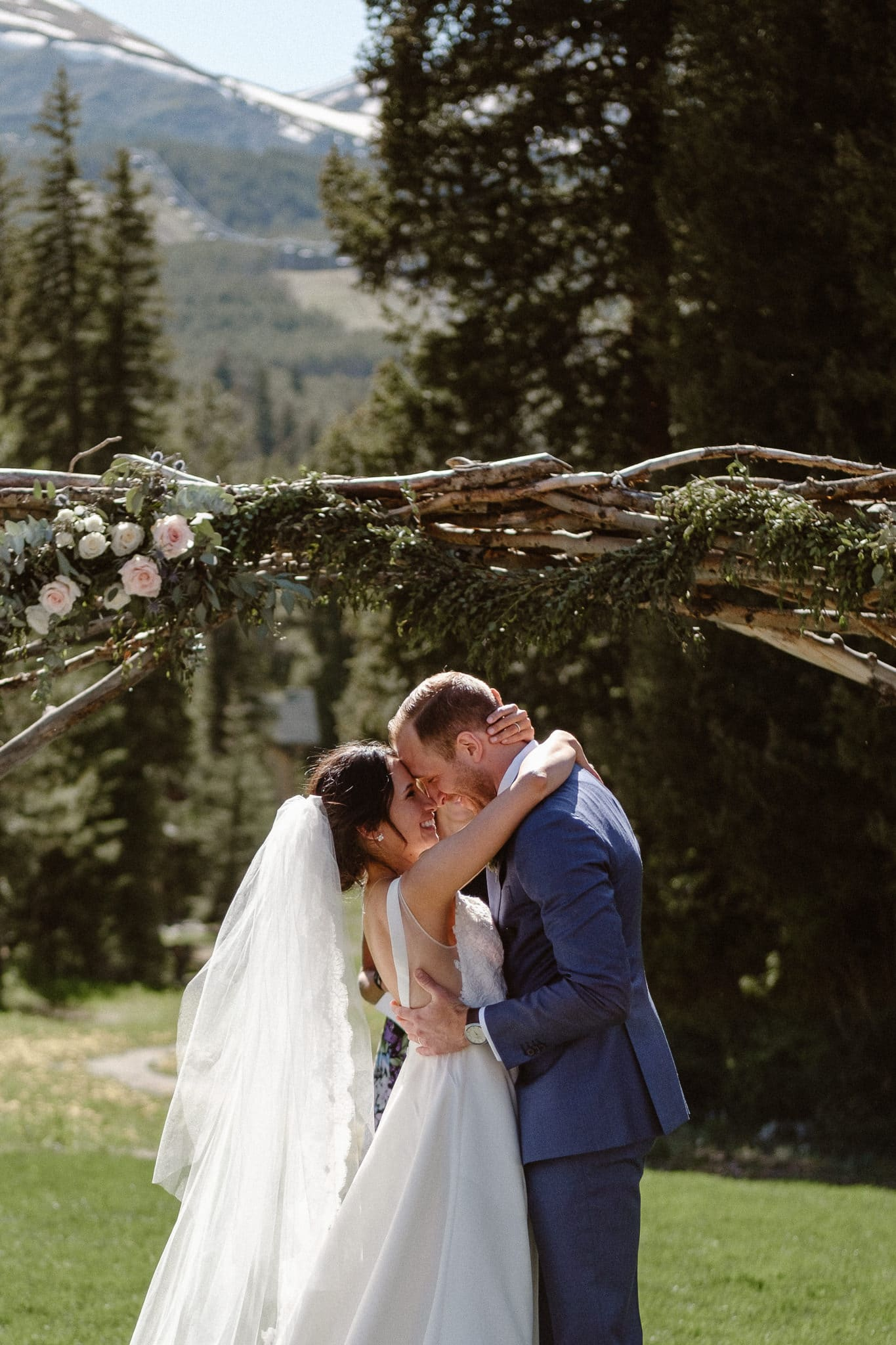 Bride and groom first kiss at Breckenridge Nordic Center wedding, Summit County wedding photographer