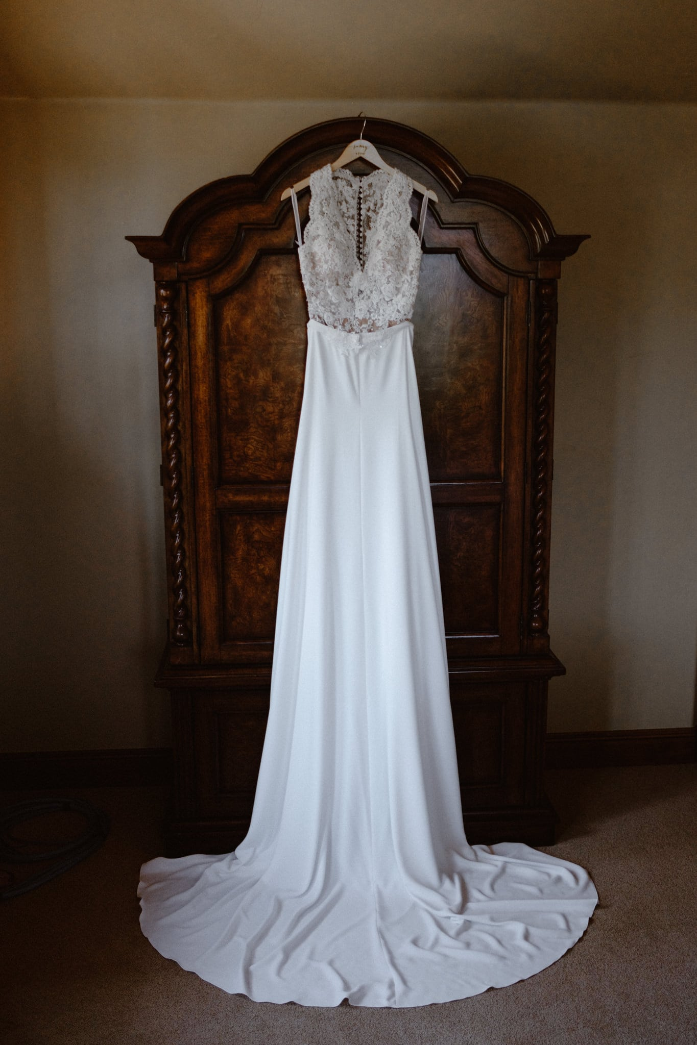 Wedding dress hanging on armoire, lace body suit and long sleek skirt