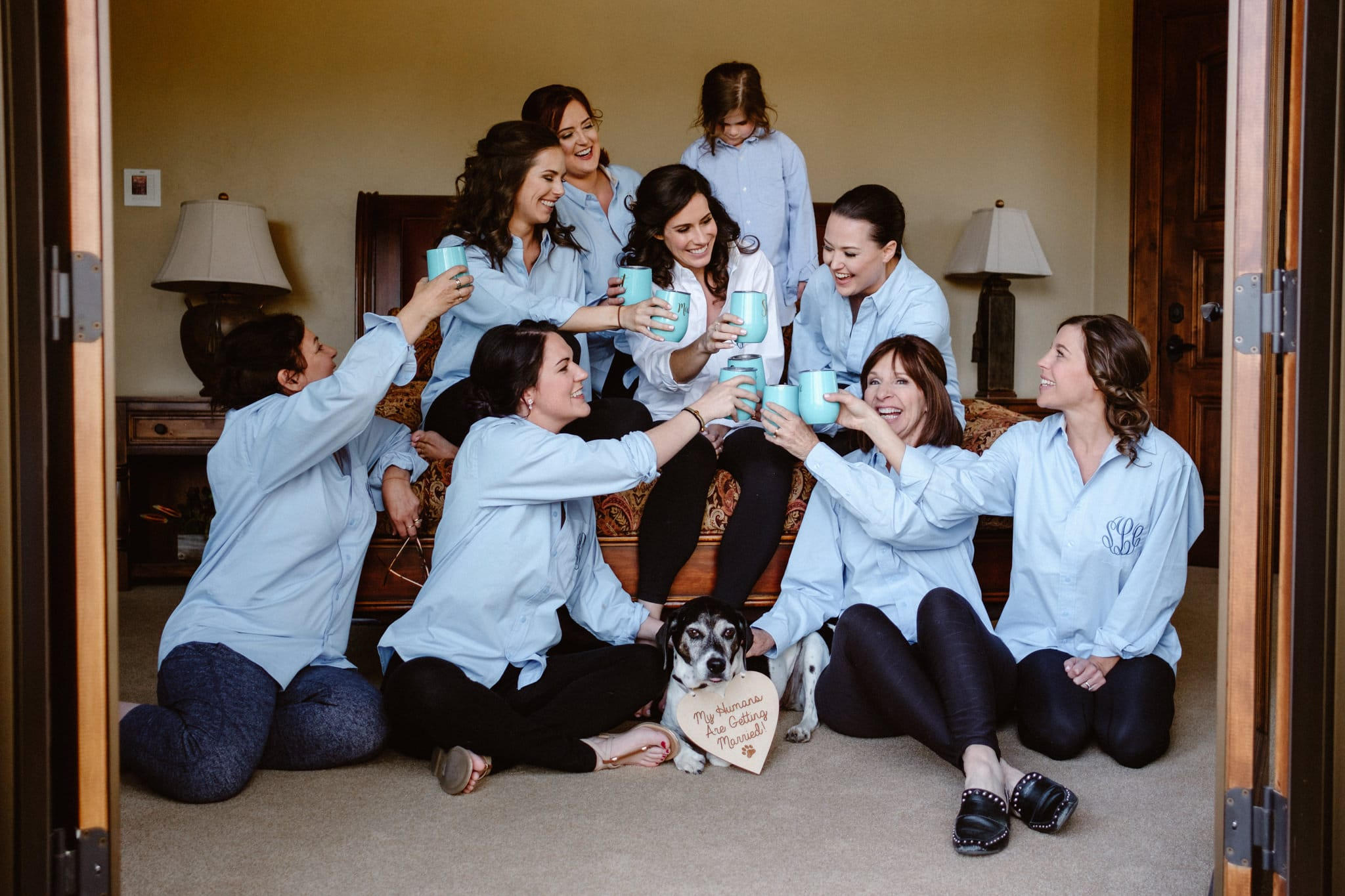 Bride and bridesmaids in matching monogrammed shirts while getting ready