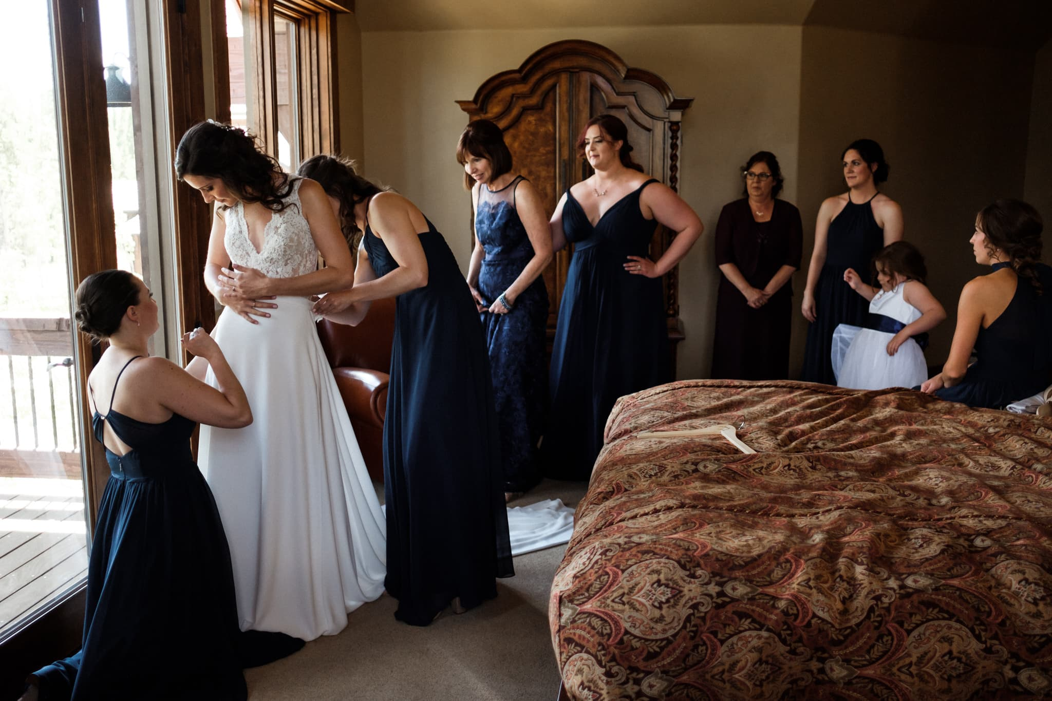Bride surrounded by bridesmaids while getting ready, Breckenridge wedding photographer Colorado