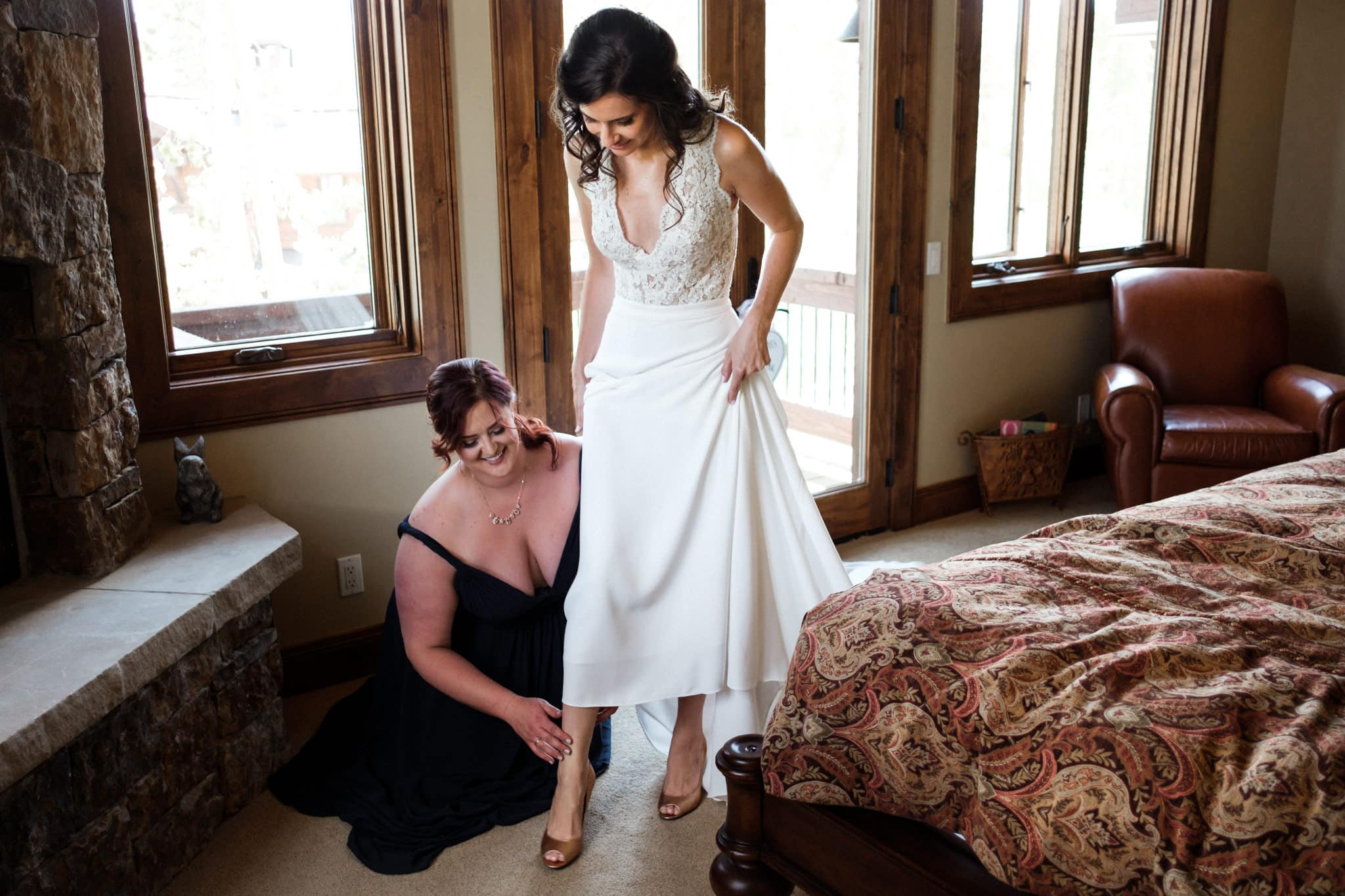 Bridesmaid helping bride put her shoes on, Colorado wedding photographer
