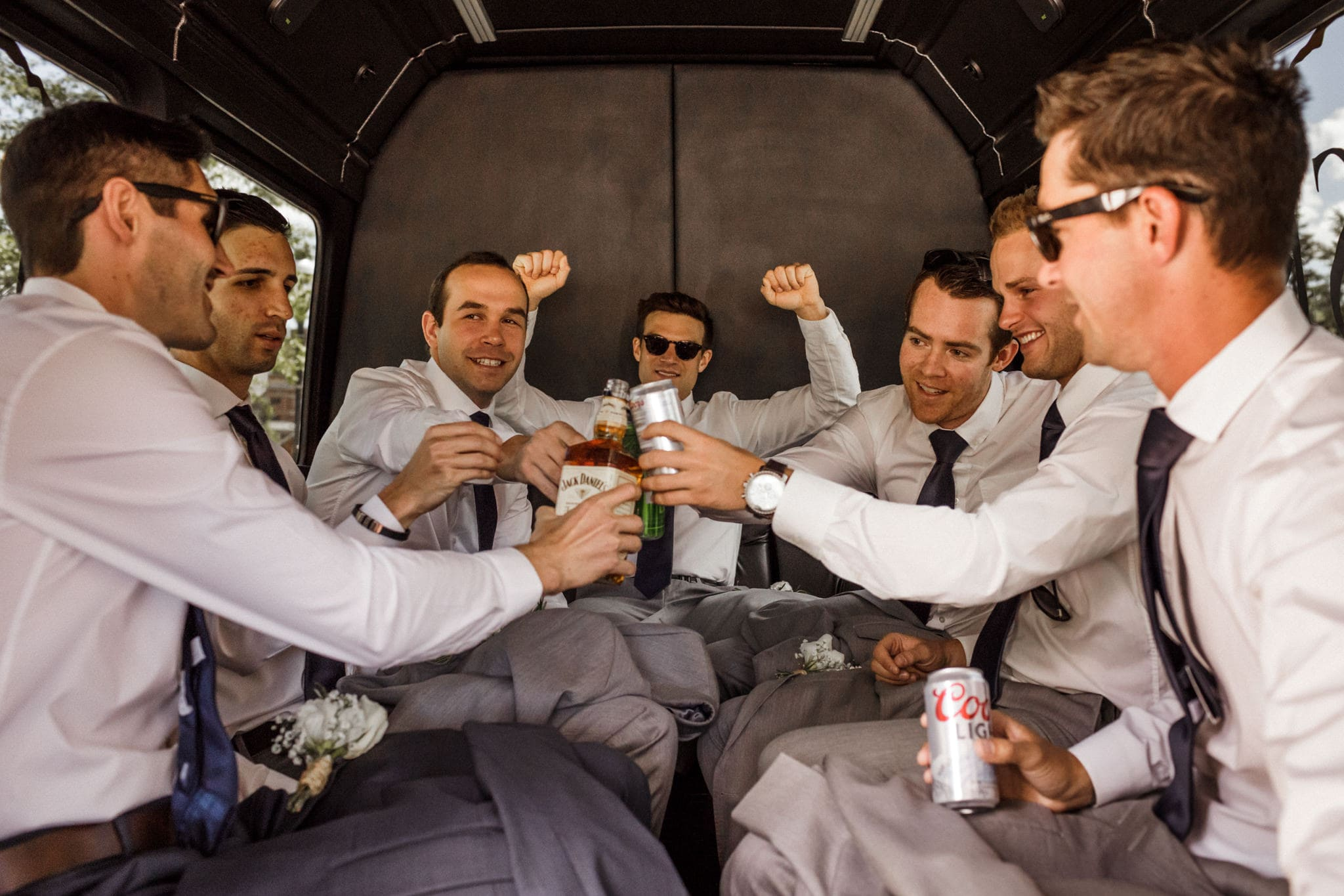 Groom and groomsmen drinking in shuttle on the way to a Main Street Station wedding in Breckenridge