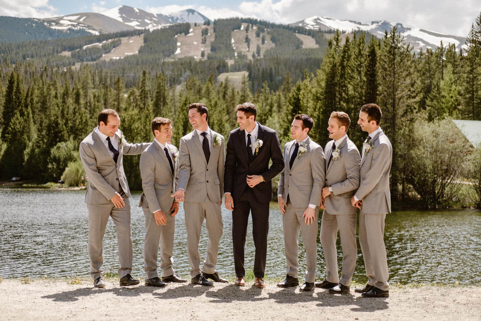 Groom in navy blue suit and groomsmen in light gray suits, wedding party photos, Breckenridge wedding photographer at Sawmill Reservoir