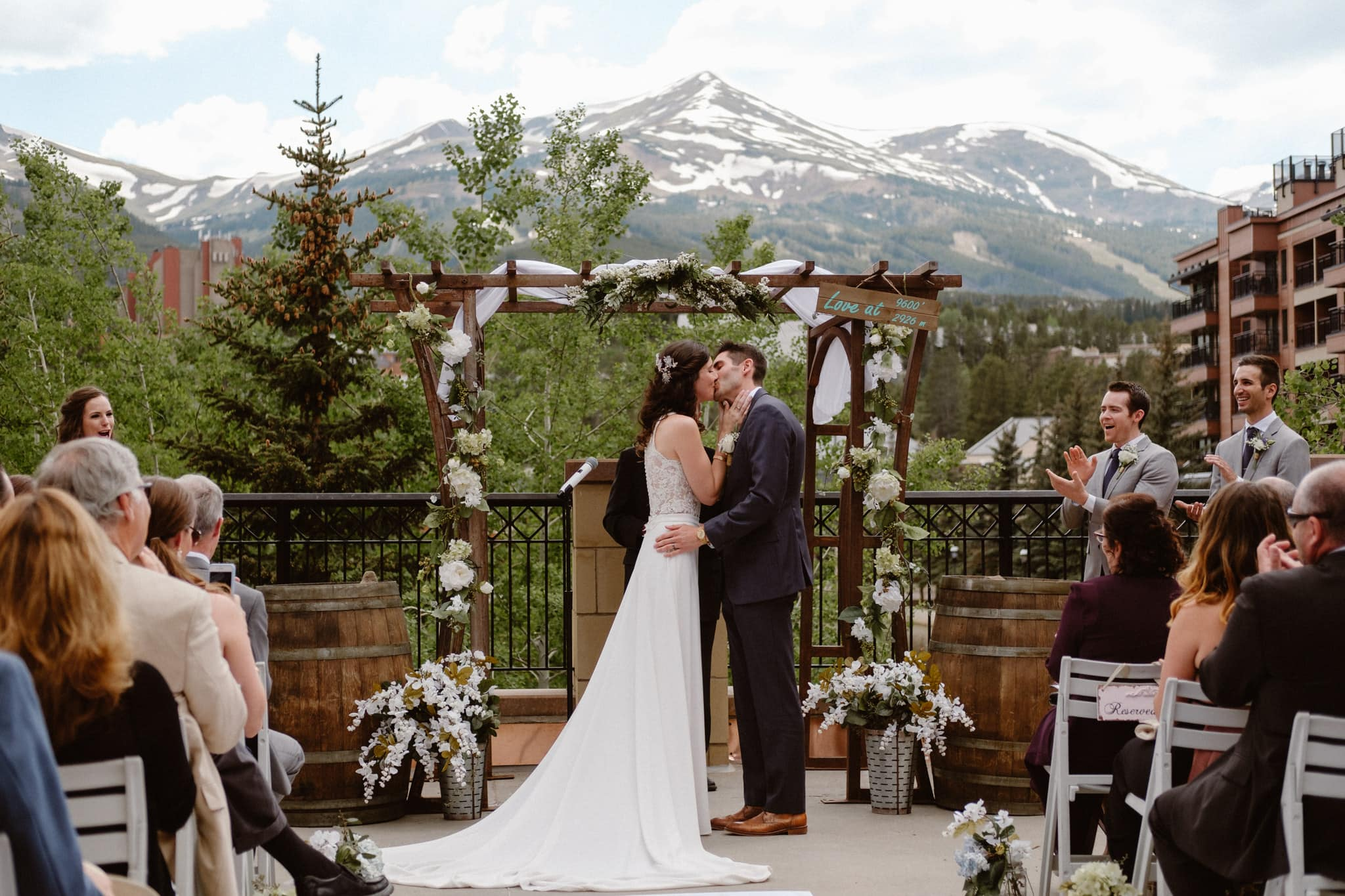 Bride and groom first kiss at Main Street Station wedding ceremony, Breckenridge Colorado ski resort wedding photographer