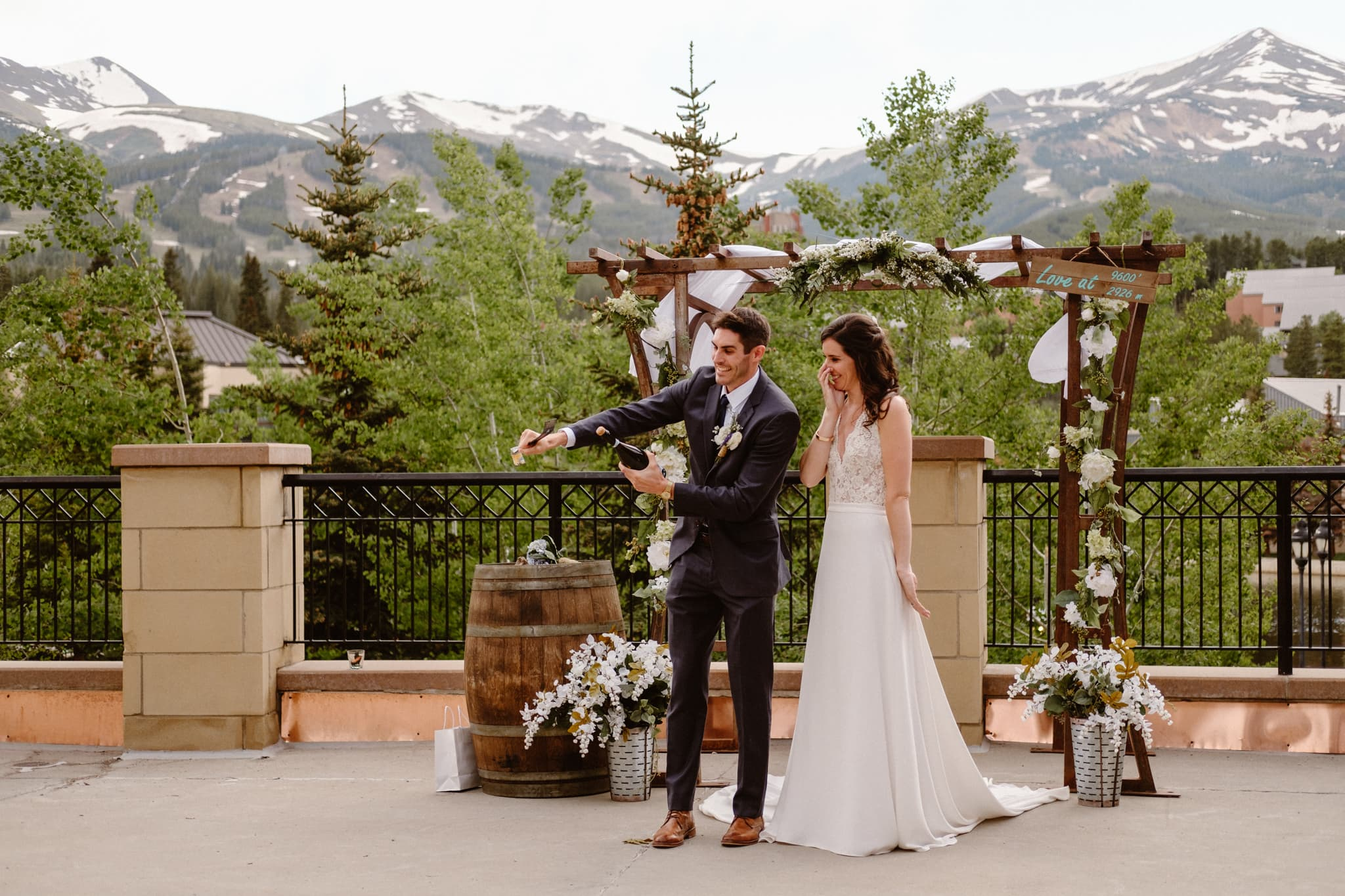 Groom attempting to pop champagne bottle with crowbar, bride cringing watching him, Main Street Station wedding venue in Breckenridge, Colorado wedding photographer