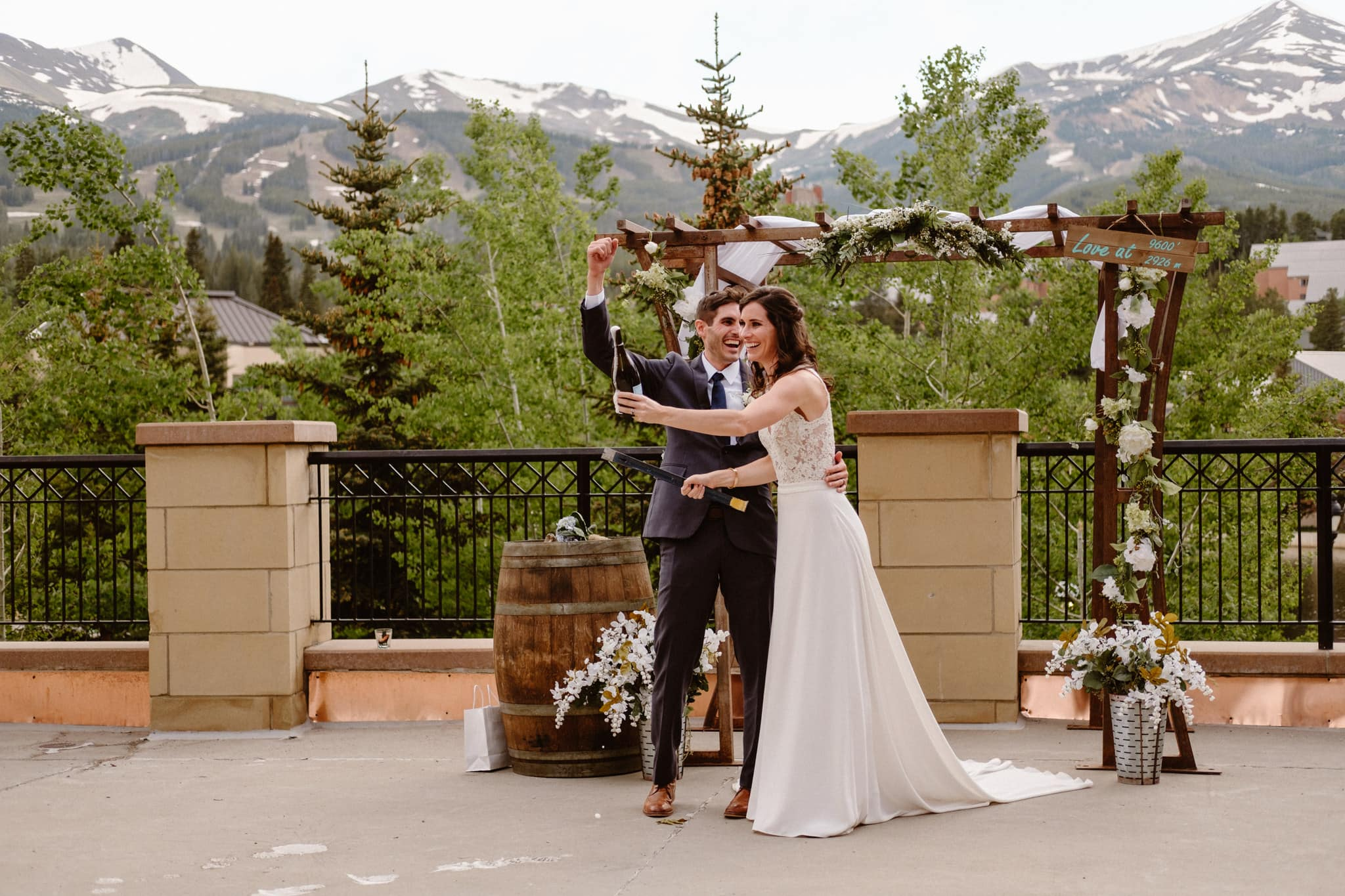 Bride popping champagne bottle with crowbar with groom watching, Main Street Station wedding venue in Breckenridge, Colorado wedding photographer