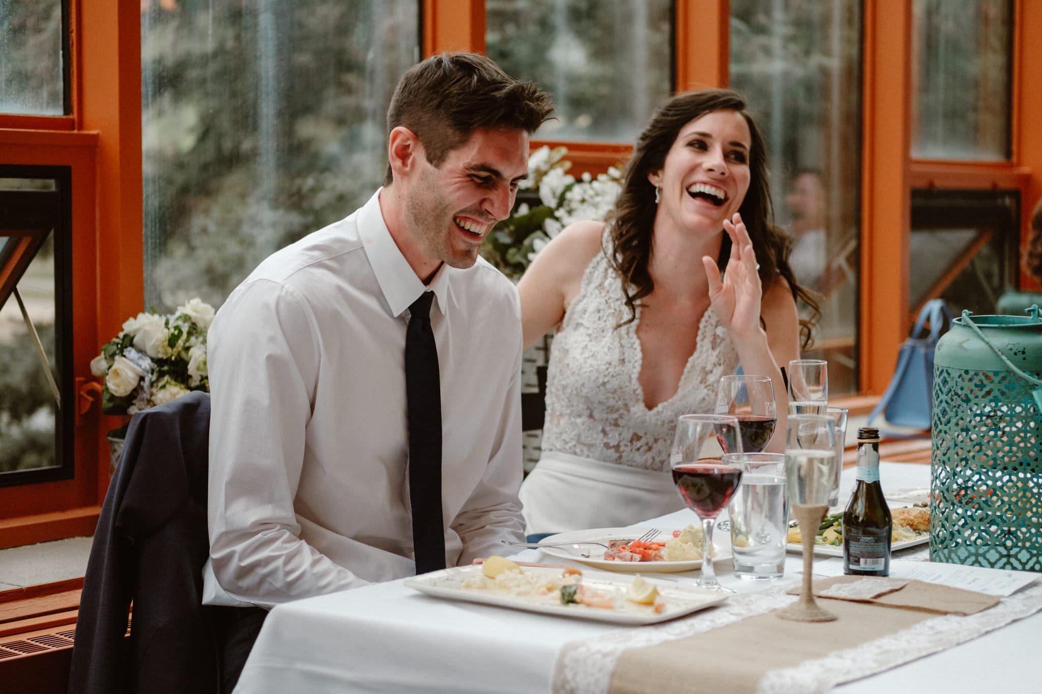 Bride and groom laughing during toast at Sauce on the Maggie, Breckenridge wedding photographer