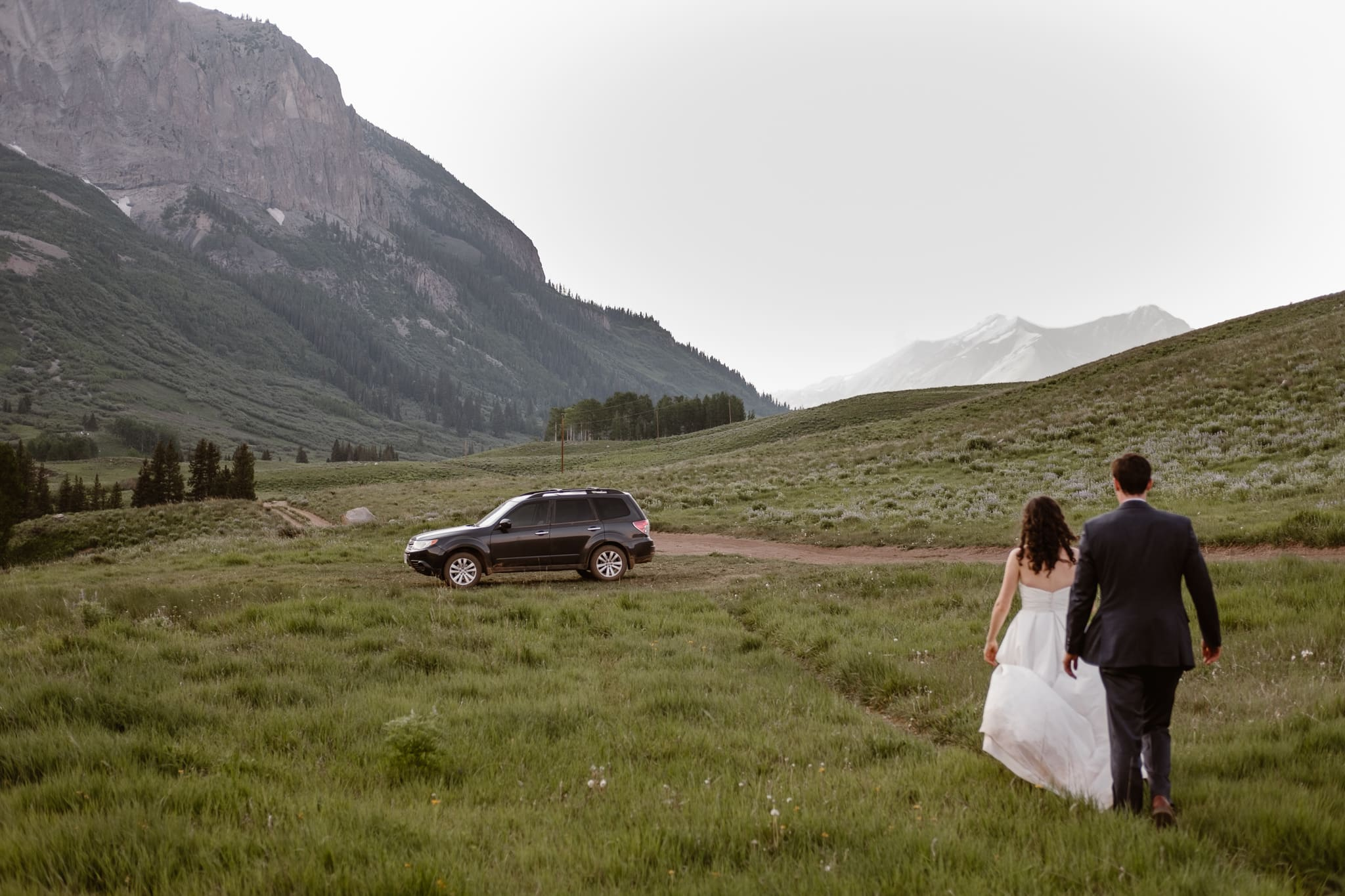 Crested Butte elopement photographer, Colorado adventure wedding photographer, bride and groom hiking to Subaru at sunset