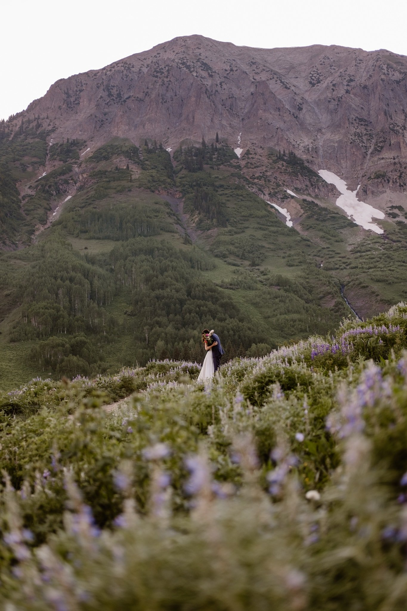 Crested Butte elopement photographer, Colorado adventure wedding photographer, bride and groom walking through wildflowers