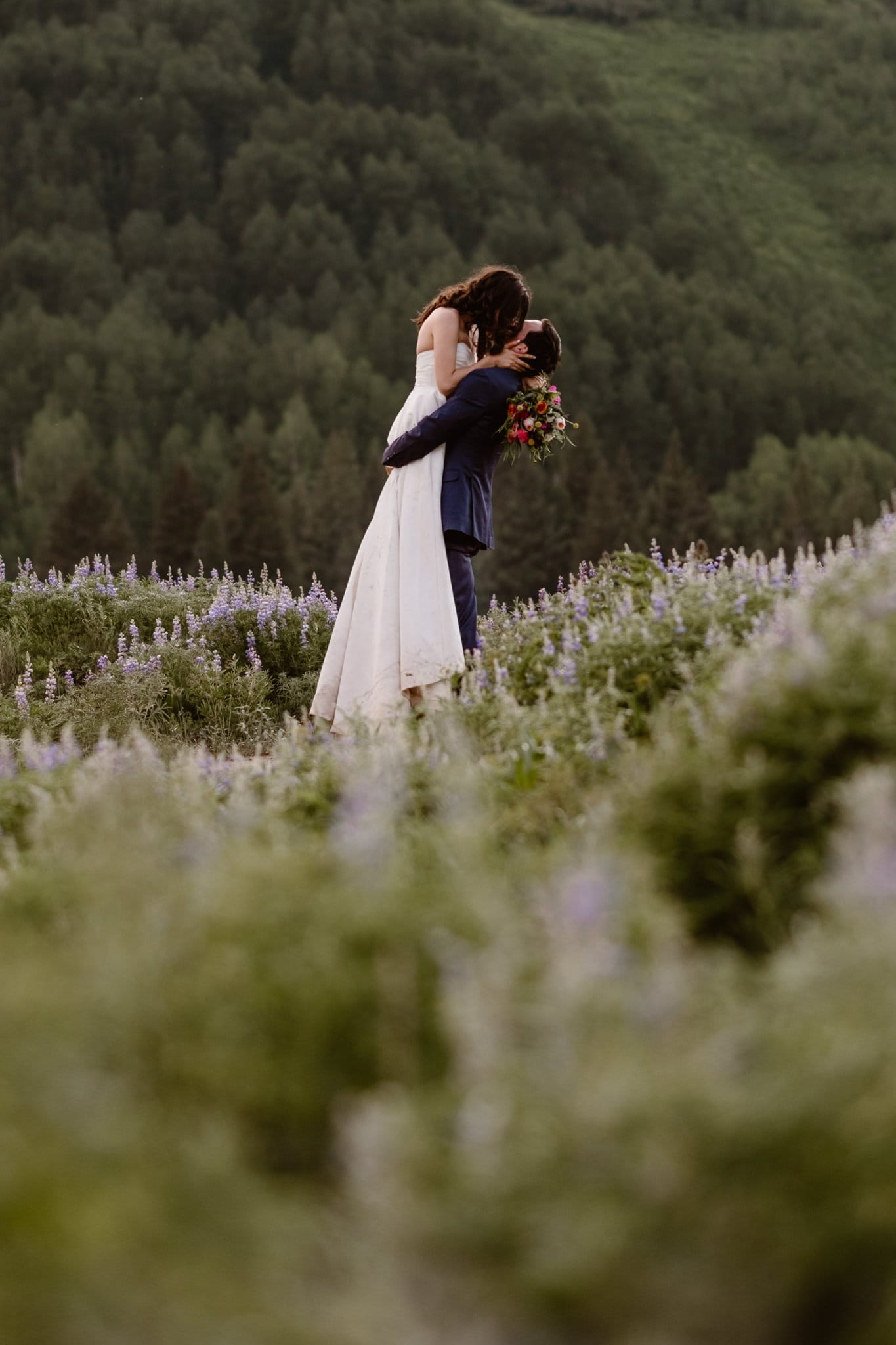 Crested Butte elopement photographer, Colorado adventure wedding photographer, bride and groom kissing in field of wildflowers