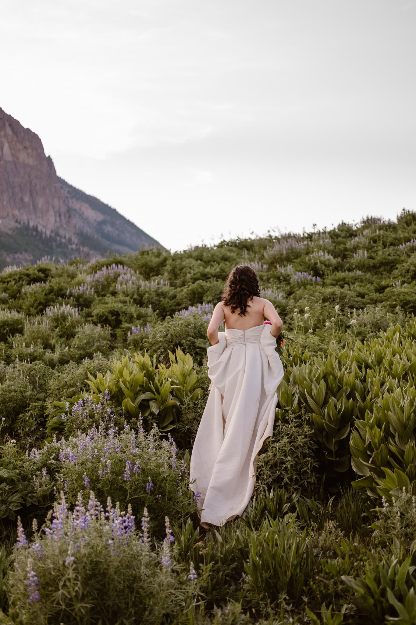 Crested Butte elopement photographer, Colorado adventure wedding photographer, bride hiking through wildflowers