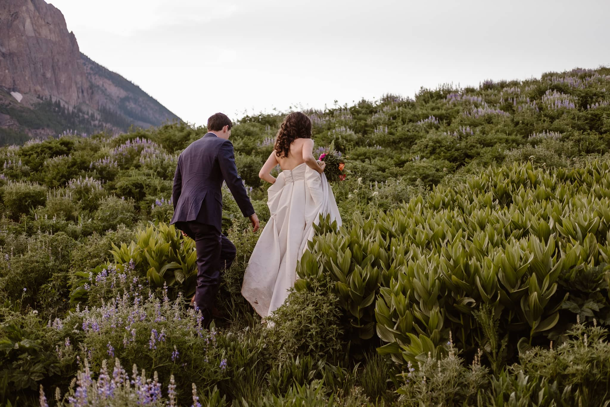 Crested Butte elopement photographer, Colorado adventure wedding photographer, bride and groom hiking through wildflowers