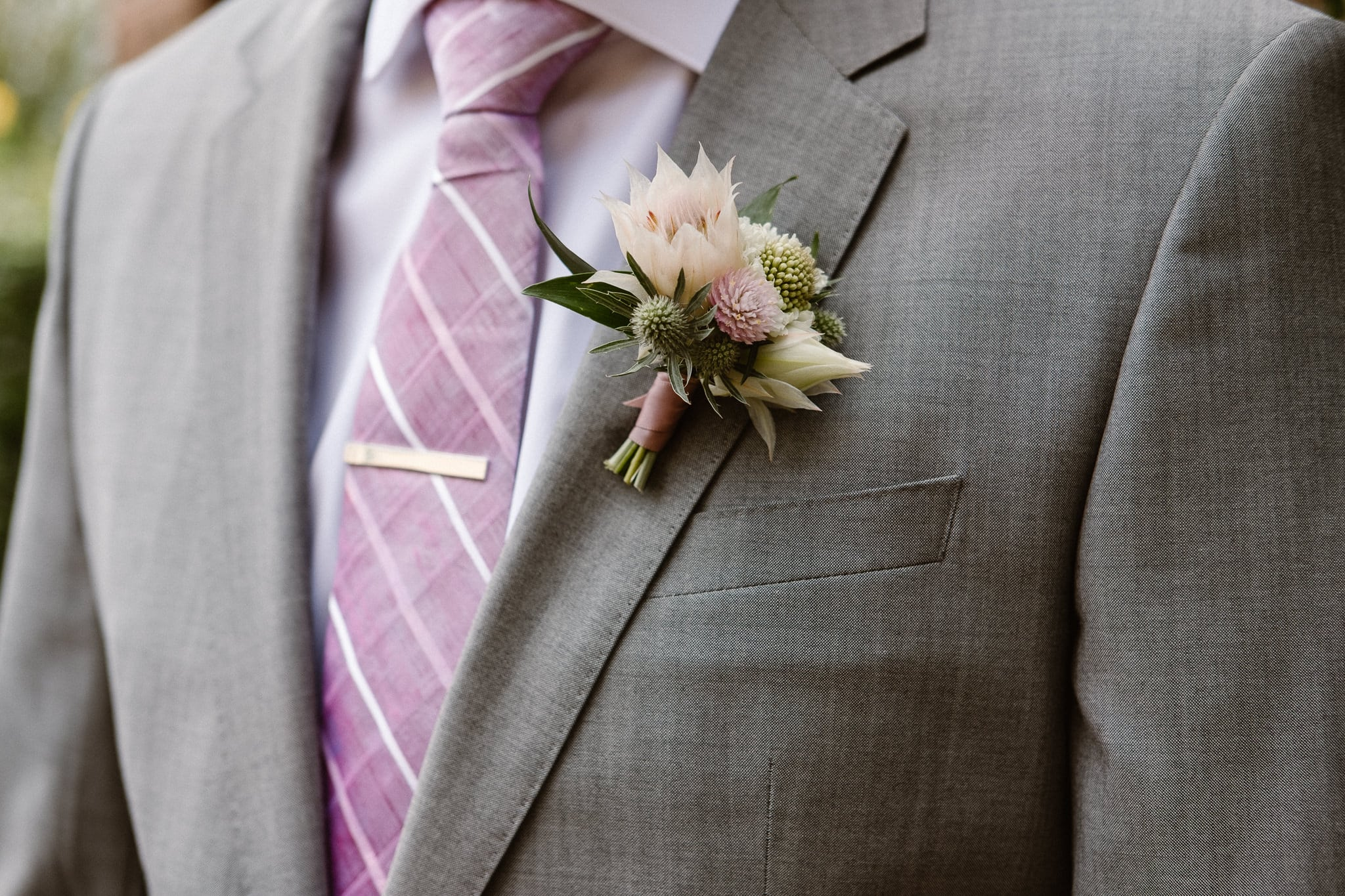 Groom getting ready for Colorado mountain elopement at St. Julien Hotel, Boulder wedding photographer, groom portrait, pale pink boutonniere by Fawns Leap