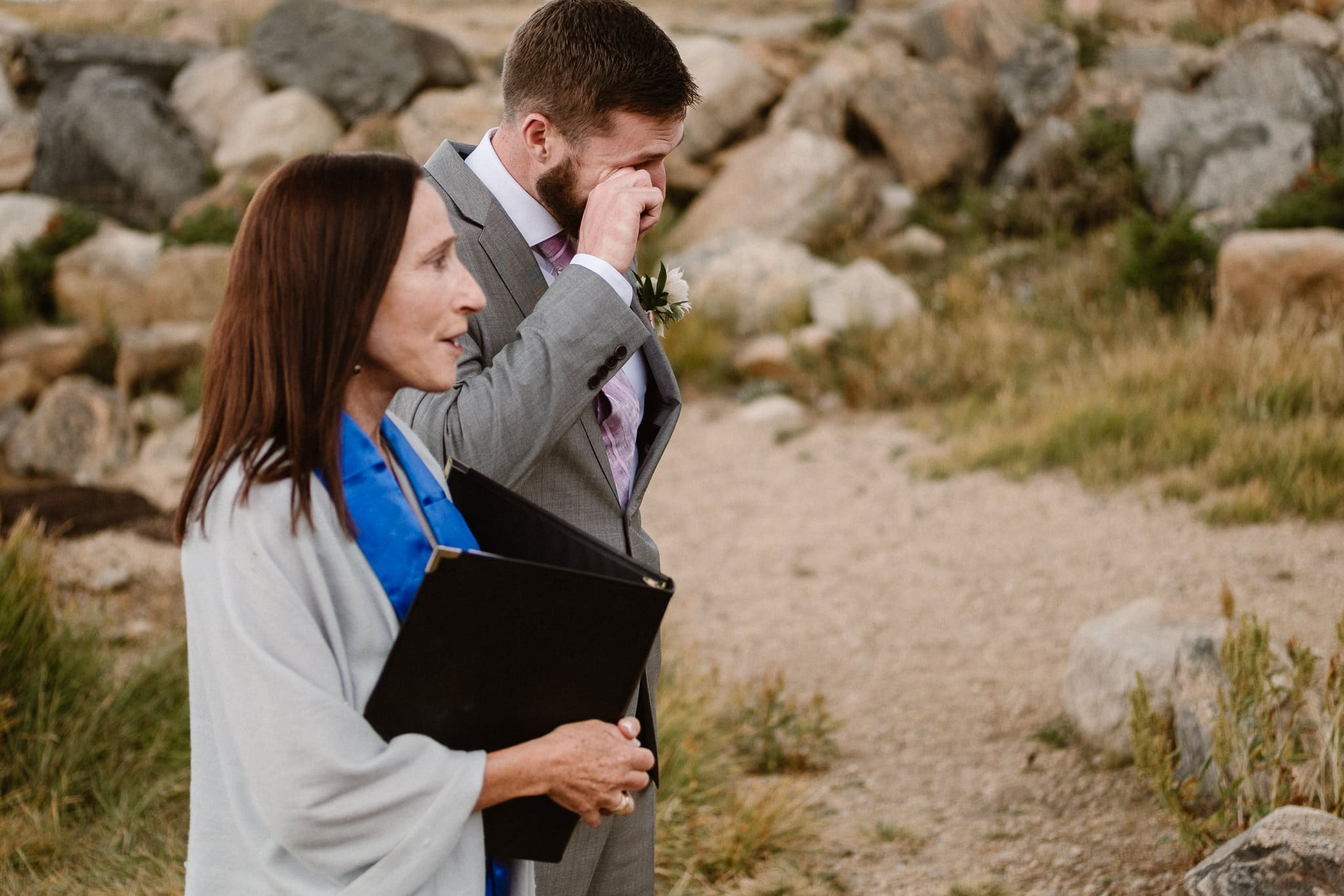 Groom watching bride walk down aisle at Colorado mountain elopement, Boulder wedding photographer, alpine lake adventure elopement, groom wiping tear