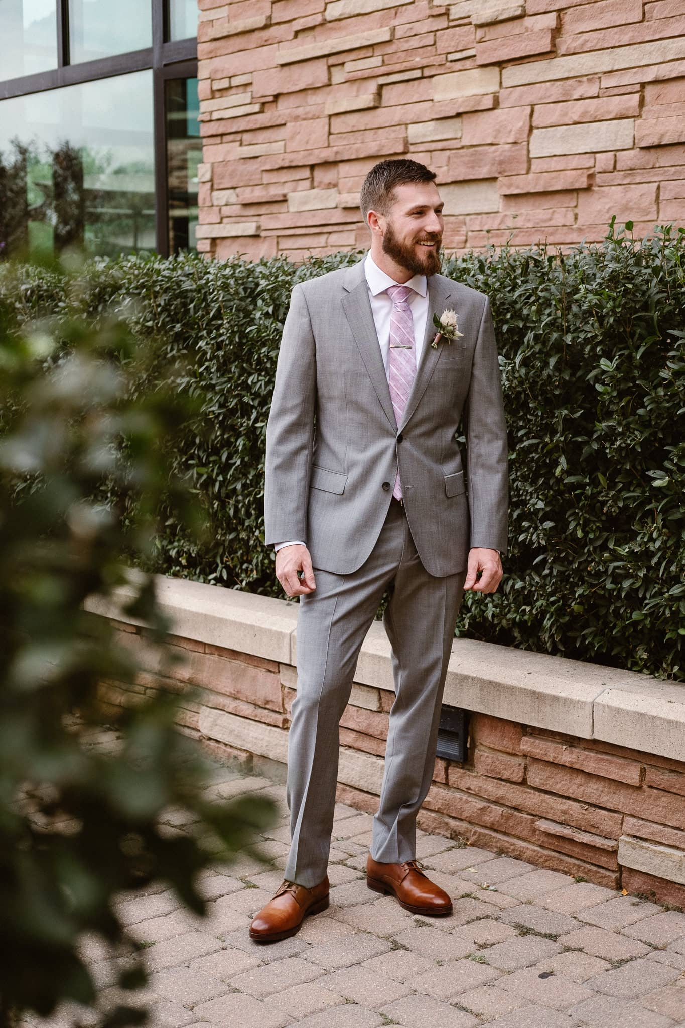 Groom getting ready for Colorado mountain elopement at St. Julien Hotel, Boulder wedding photographer, groom portrait, groom wearing gray suit and pale purple tie