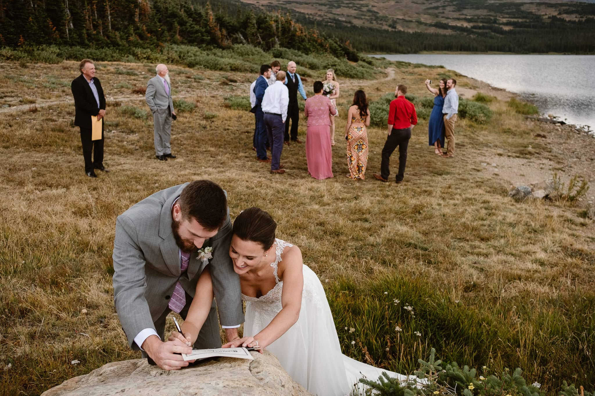 Colorado mountain elopement photographer, alpine lake adventure wedding, Boulder wedding photographer, outdoor ceremony, bride and groom signing marriage license