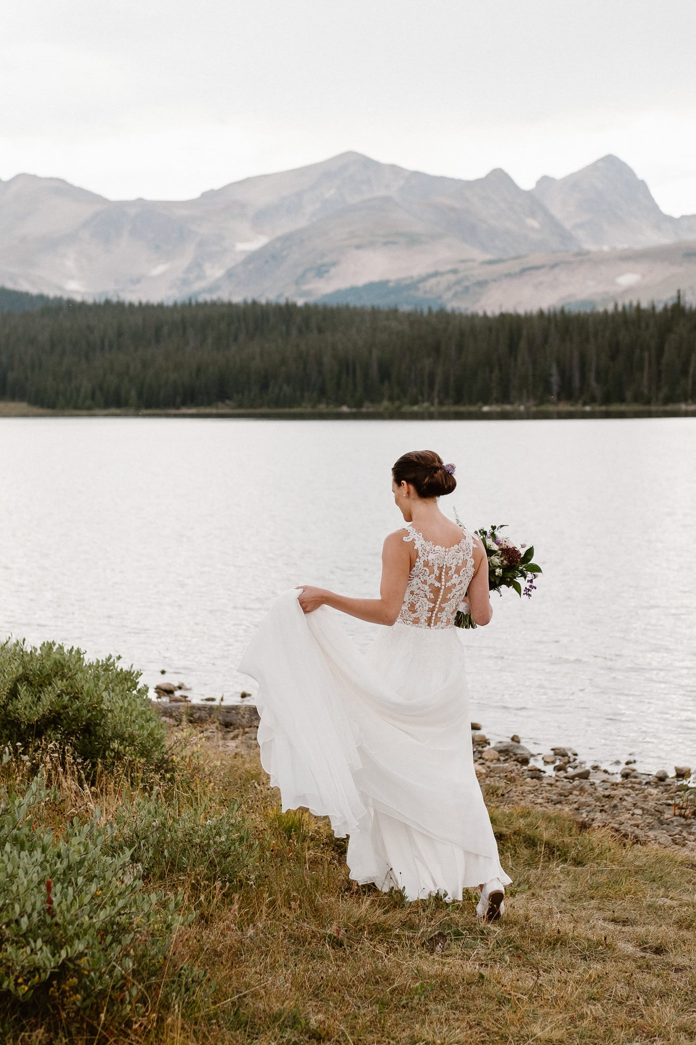 Colorado mountain elopement photographer, alpine lake adventure wedding, Boulder wedding photographer, bride walking along alpine lake, bride portrait, wedding dress with lace back
