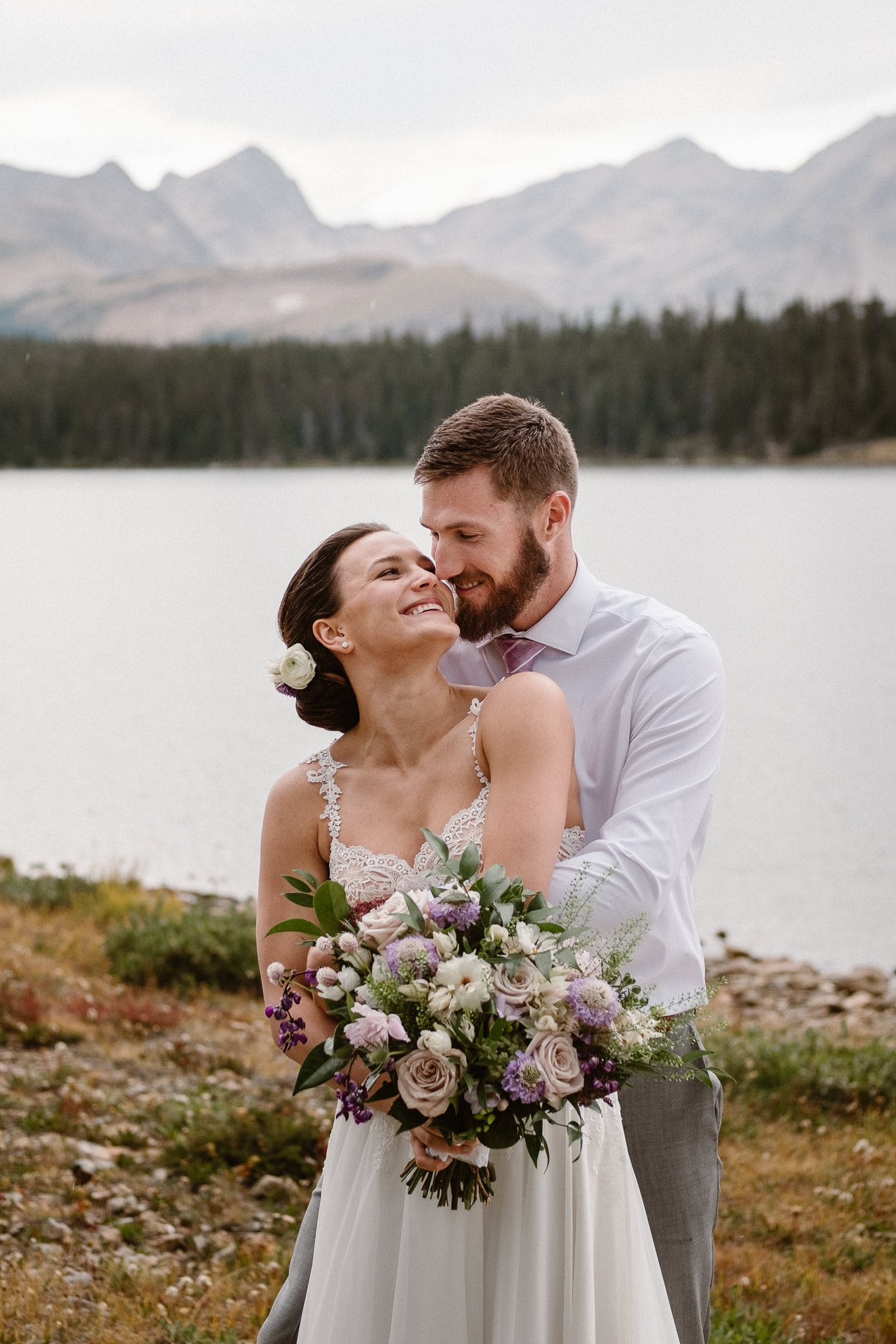Colorado mountain elopement photographer, alpine lake adventure wedding, Boulder wedding photographer, bride and groom portraits in mountains, laidback boho wedding, hiking elopement, bouquet by Fawns Leap, pale pink and purple florals